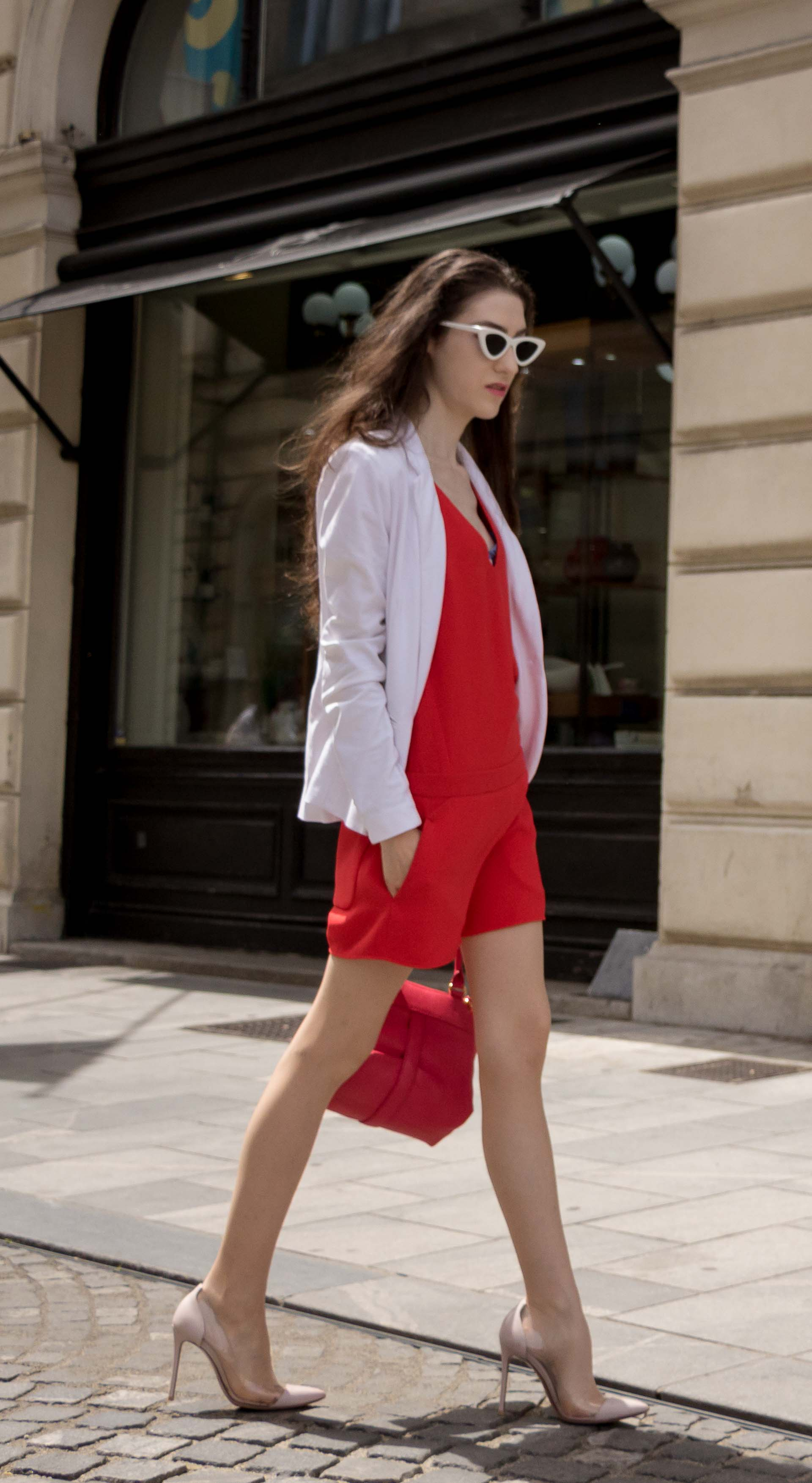 Veronika Lipar Fashion Editor of Brunette from Wall Street dressed in red playsuit, white blazer, Adam Selman x Le Specs white cat eye Lolita sunglasses, pink top handle See by Chloe bag, Gianvito Rossi plexi pumps on the street in Ljubljana