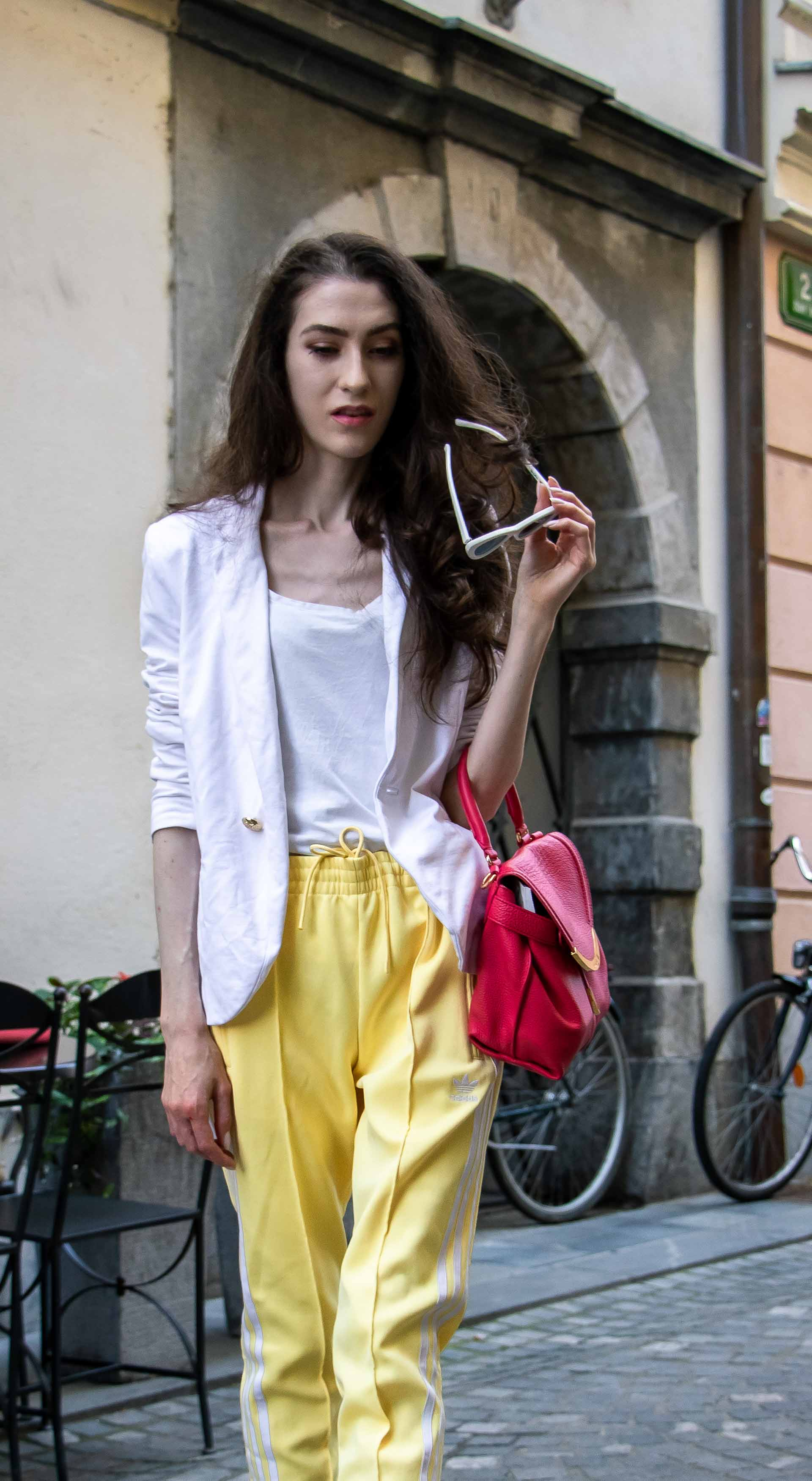 Veronika Lipar Fashion Blogger of Brunette from Wall Street wearing chic casual white blazer, white H&M t-shirt, yellow Addidas track pants, See by Chloé pink top handle bag, Adam Selman x Le Specs white cat eye Lolita sunglasses, pink blush Gianvito Rossi plexi pumps on the street