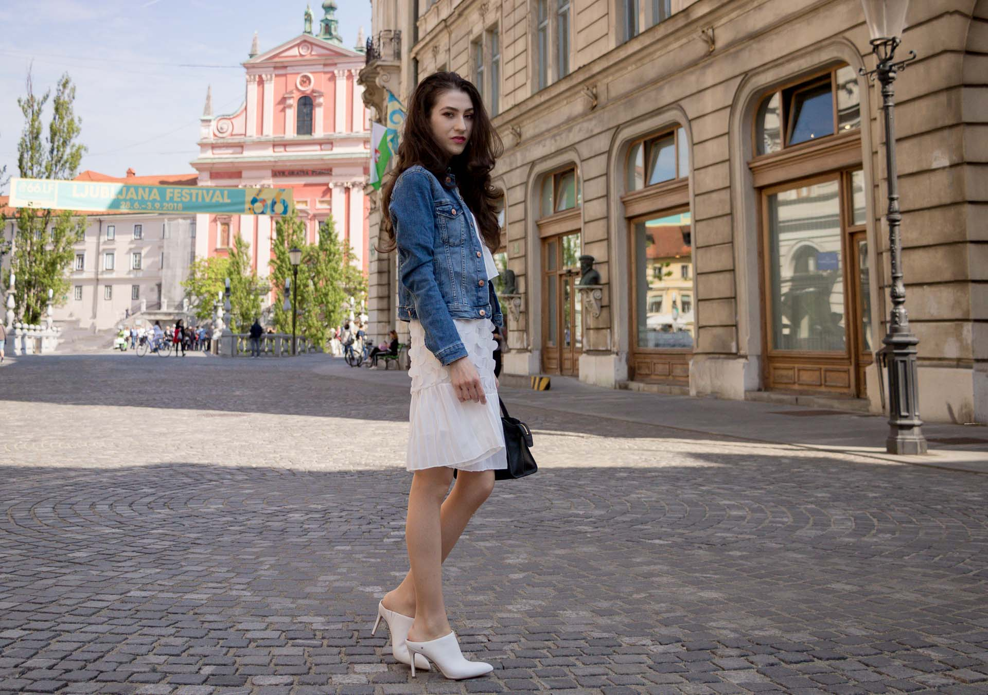 Veronika Lipar Fashion Editor of Brunette from Wall Street dressed in H&M blue denim jacket, Storets white pleated short dress, white mules and Adam Selman x Le Specs white cat eye Lolita sunglasses, black small bag