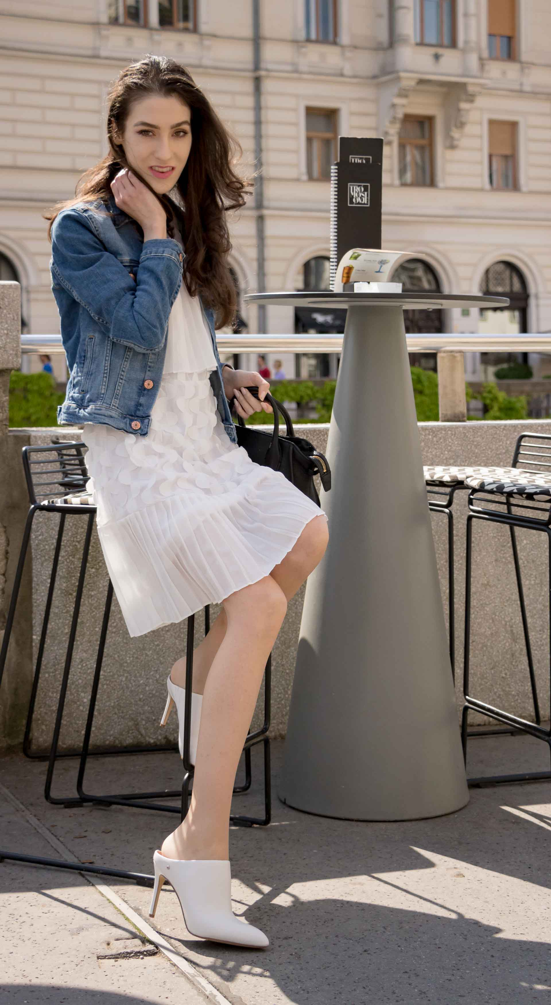 Veronika Lipar Fashion Editor of Brunette from Wall Street dressed in H&M blue denim jacket, Storets white pleated short dress, white mules and Adam Selman x Le Specs white cat eye Lolita sunglasses, black small bag sitting at the bar on the street
