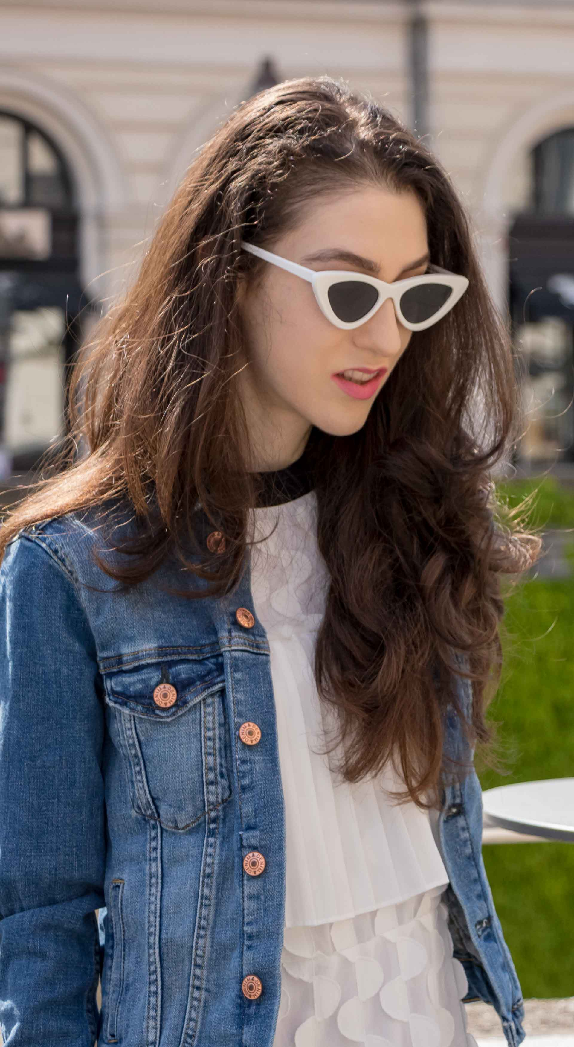 Veronika Lipar Fashion Editor of Brunette from Wall Street wearing H&M blue denim jacket, Storets white pleated short dress, cat eye sunglasses