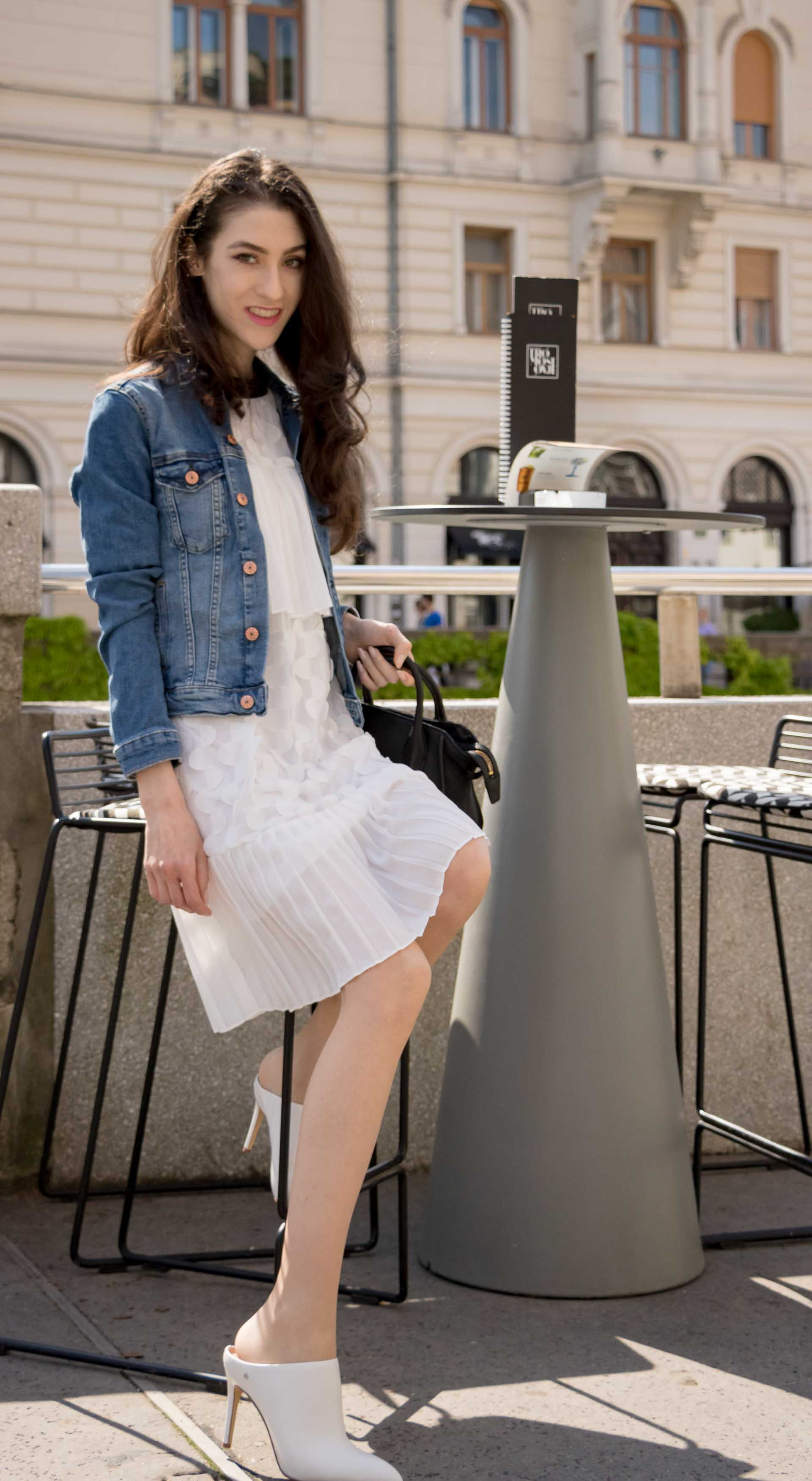 Veronika Lipar Fashion Editor of Brunette from Wall Street dressed in H&M blue denim jacket, Storets white pleated short dress, white mules and Adam Selman x Le Specs white cat eye Lolita sunglasses, black small bag getting up from the stool