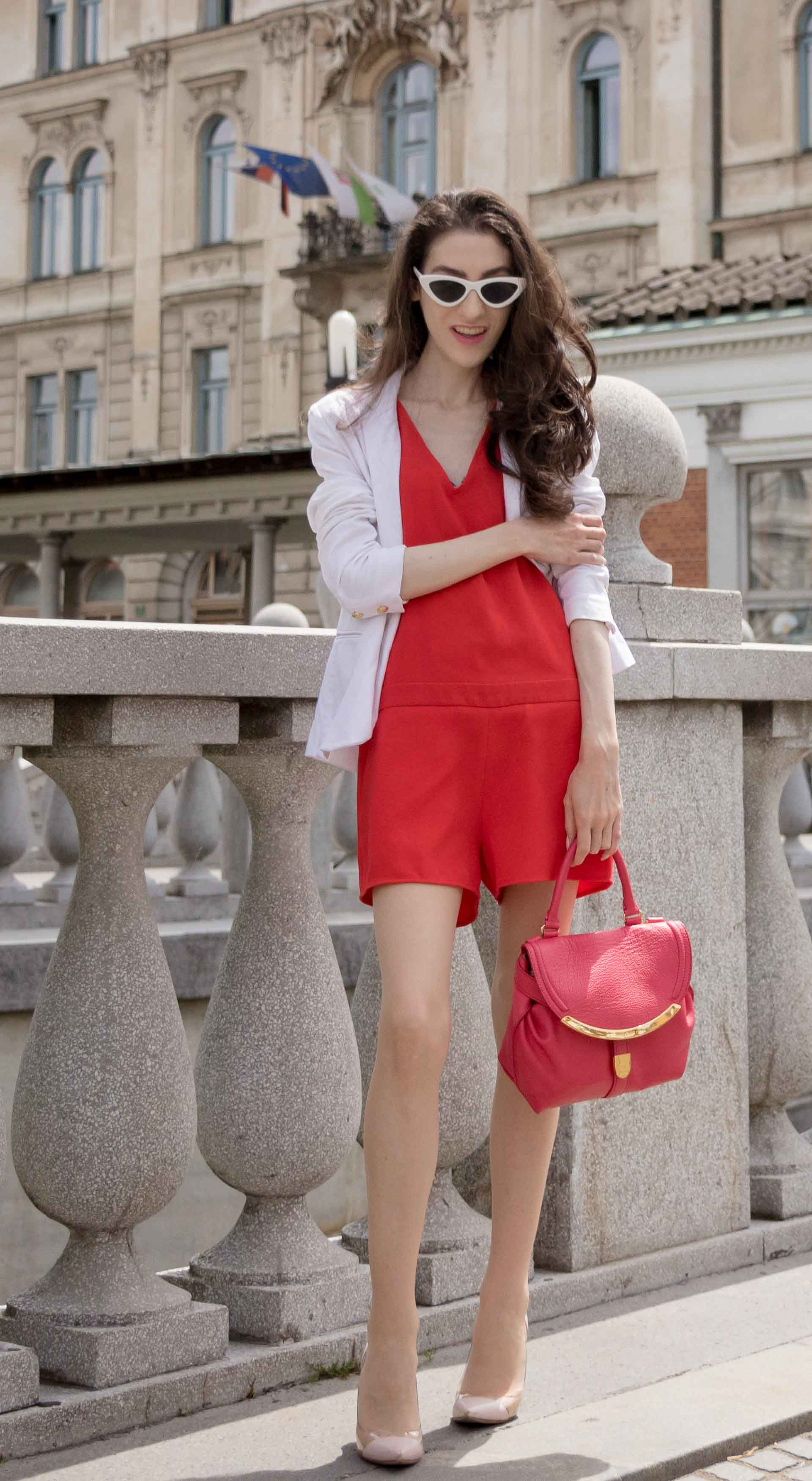 Veronika Lipar Fashion Editor of Brunette from Wall Street dressed in red playsuit, white blazer, Adam Selman x Le Specs white cat eye Lolita sunglasses, pink top handle See by Chloe bag, Gianvito Rossi plexi pumps