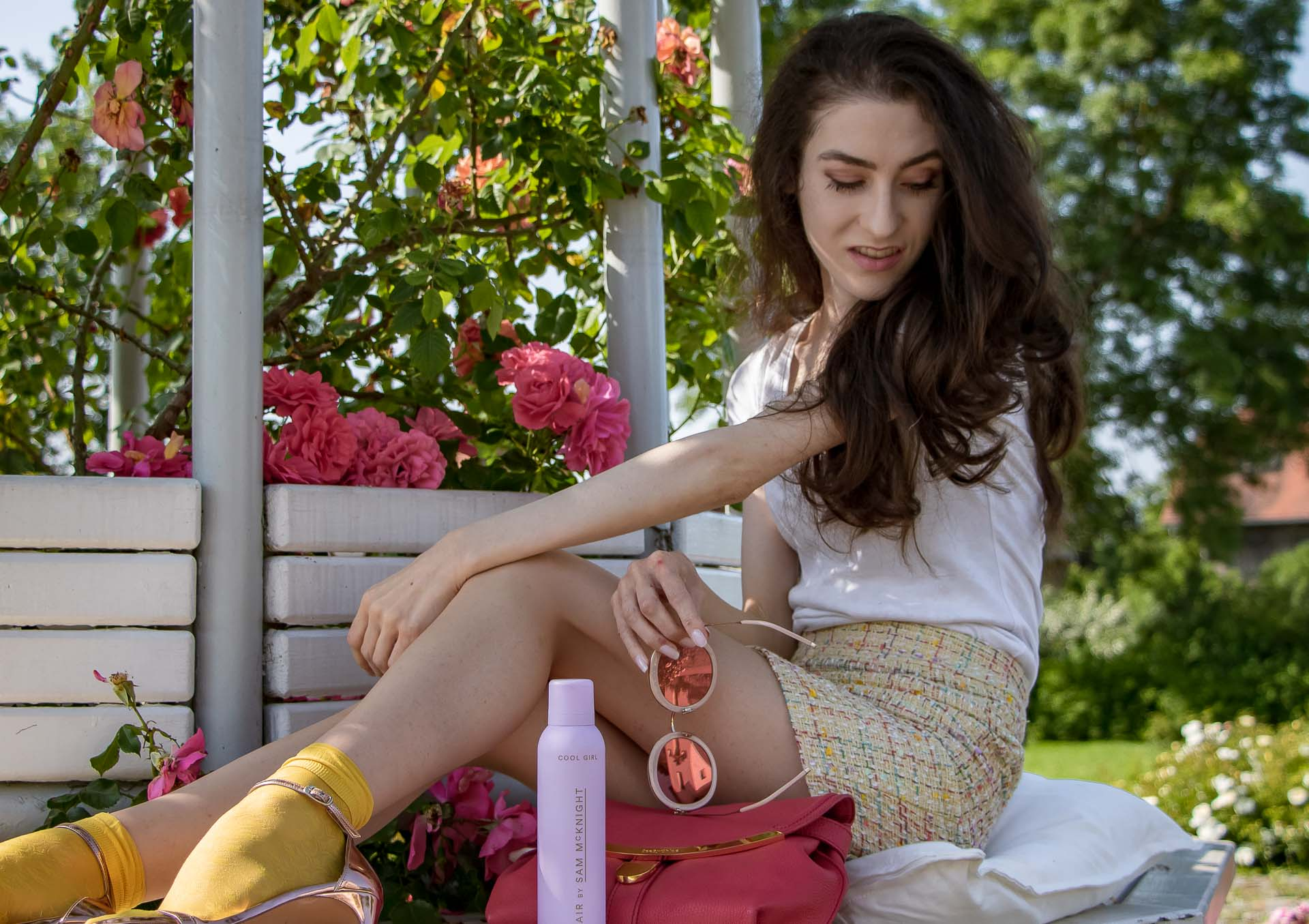 Veronika Lipar Fashion Editor of Brunette from Wall Street in rose garden wearing white t-shirt, tweed mini skirt, yellow socks and Stuart Weitzman sandals