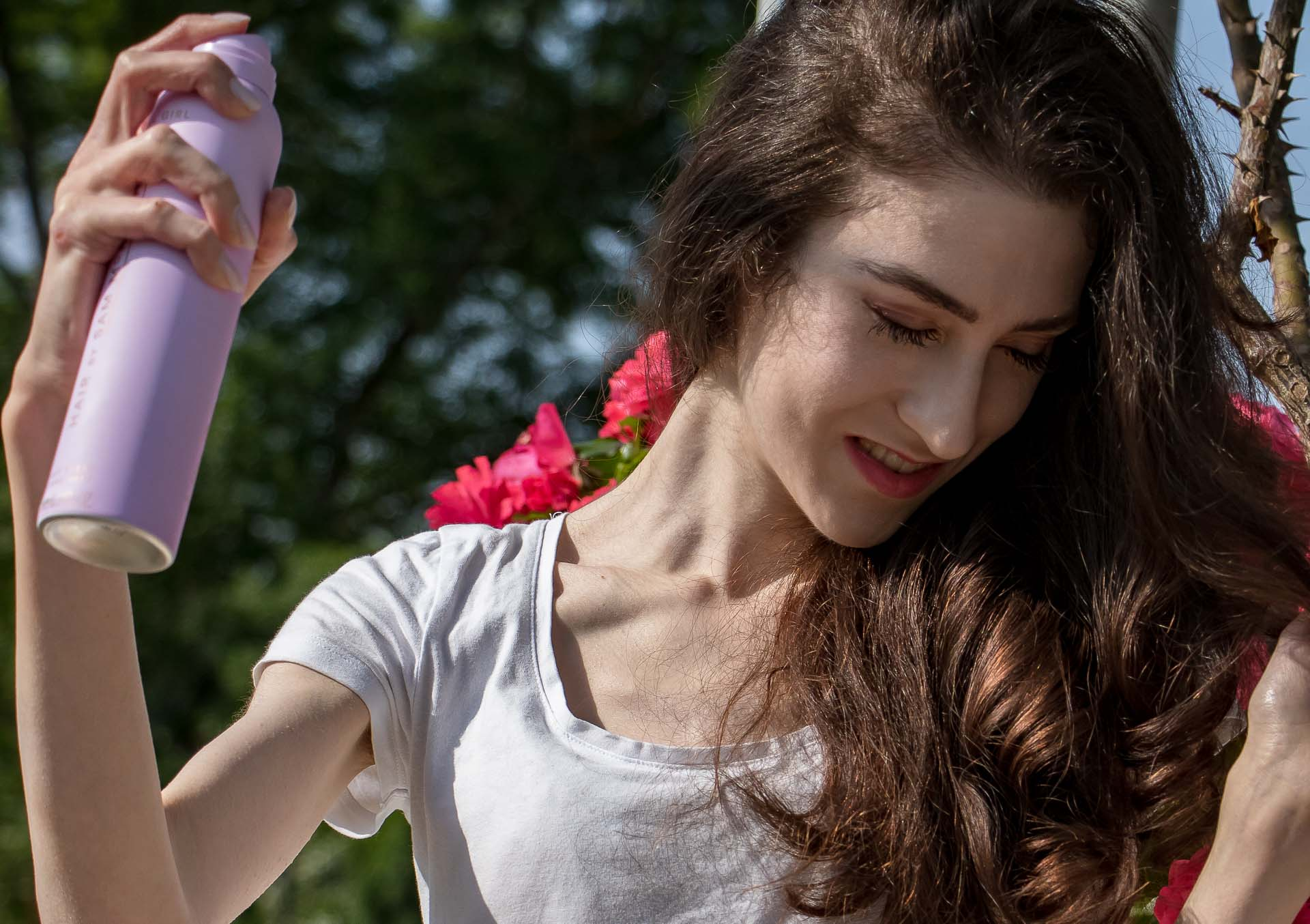 Veronika Lipar Fashion Editor of Brunette from Wall Street in rose garden wearing white t-shirt, spraying her beautiful curls with cool girl hair by sam mcknight hairspray