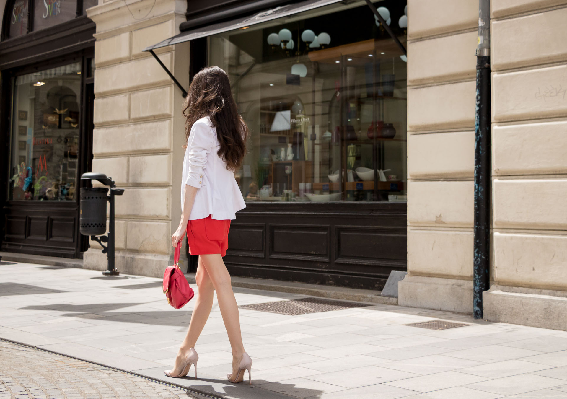 Veronika Lipar Fashion Blogger of Brunette from Wall Street dressed in red playsuit, white blazer, Adam Selman x Le Specs white cat eye Lolita sunglasses, pink top handle See by Chloe bag, Gianvito Rossi plexi pumps on the street in Ljubljana