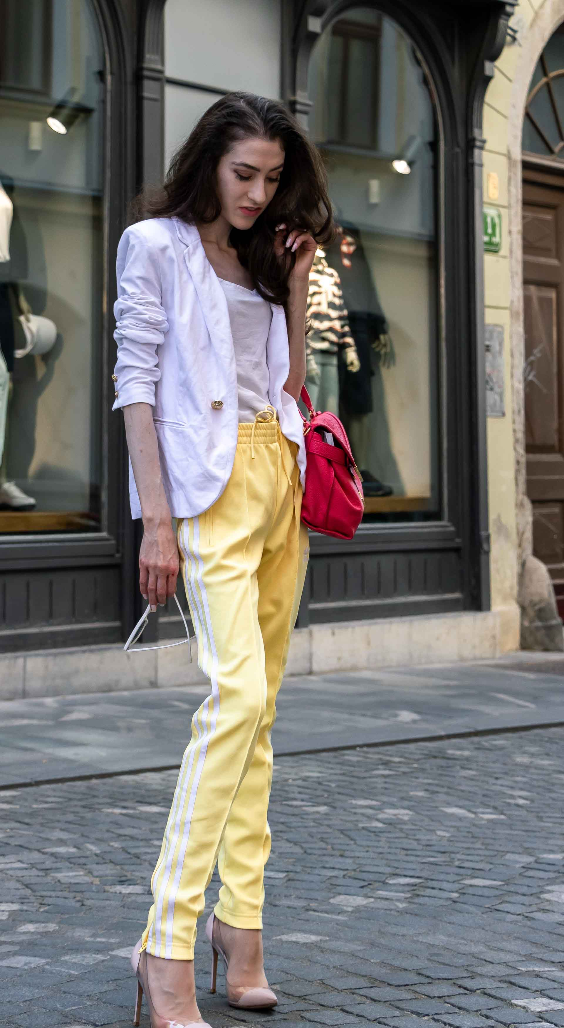 Veronika Lipar Fashion Editor of Brunette from Wall Street dressed in white blazer, white H&M t-shirt, yellow Addidas track pants, See by Chloé pink top handle bag, Adam Selman x Le Specs white cat eye Lolita sunglasses, pink blush Gianvito Rossi plexi pumps on the street in the morning