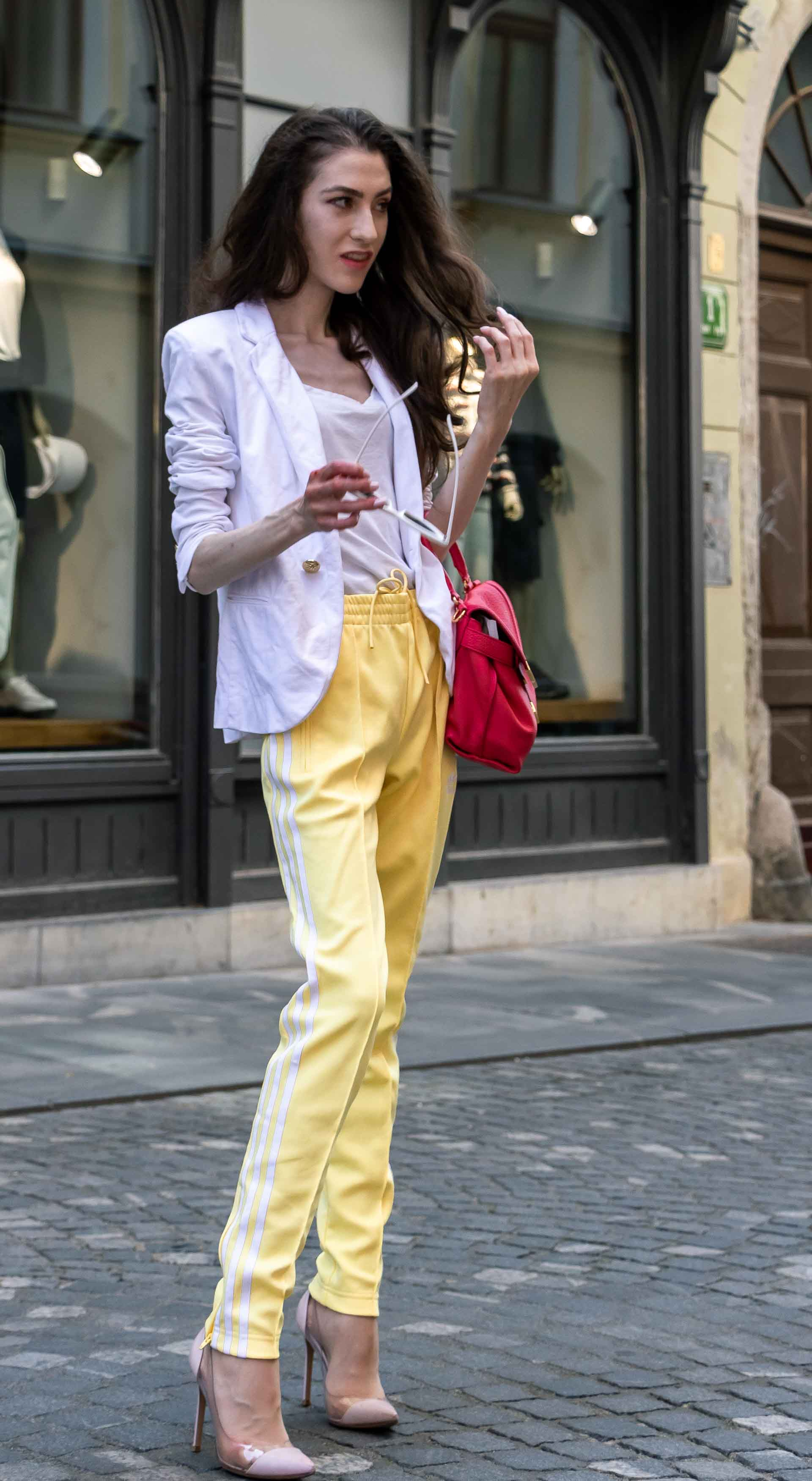Veronika Lipar Fashion Editor of Brunette from Wall Street wearing white blazer, white H&M t-shirt, yellow Addidas track pants, See by Chloé pink top handle bag, Adam Selman x Le Specs white cat eye Lolita sunglasses, pink blush Gianvito Rossi plexi pumps on the street in Ljubljana