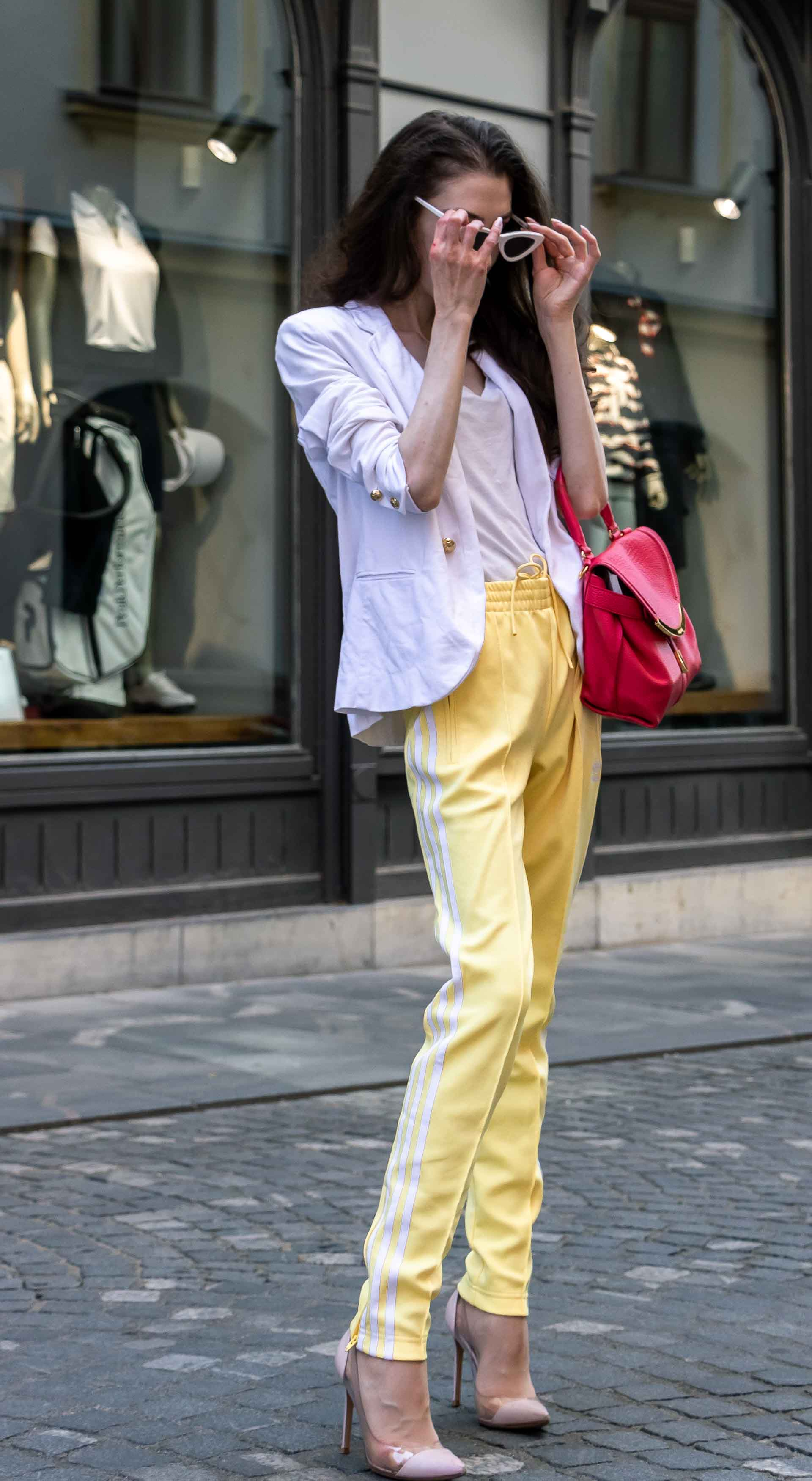Veronika Lipar Fashion Editor of Brunette from Wall Street dressed in white blazer, white H&M t-shirt, yellow Addidas track pants, See by Chloé pink top handle bag, Adam Selman x Le Specs white cat eye Lolita sunglasses, pink blush Gianvito Rossi plexi pumps in summer