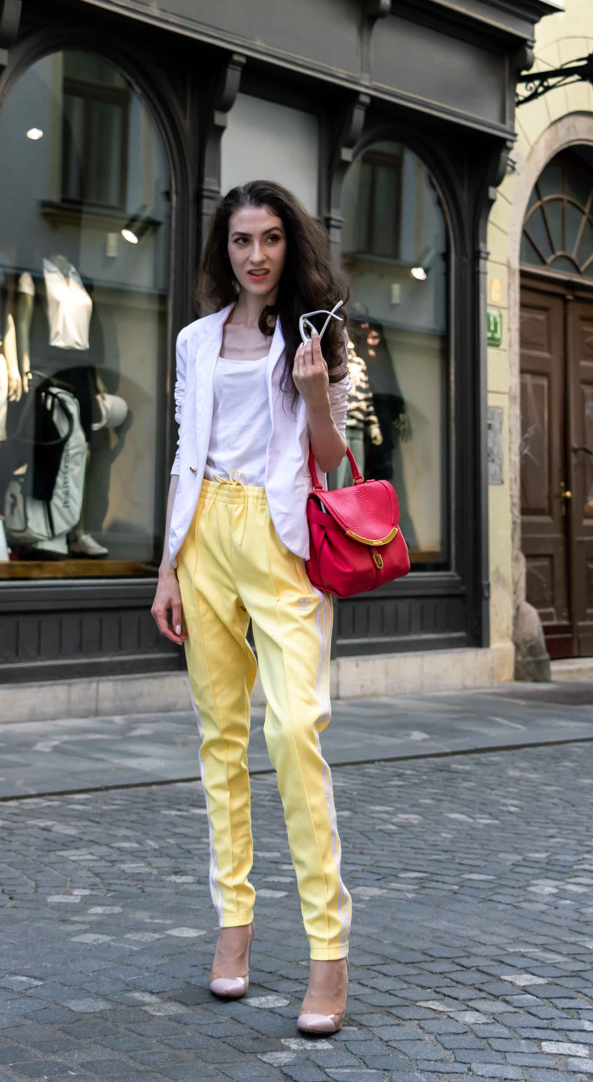 Veronika Lipar Fashion Blogger of Brunette from Wall Street dressed in white blazer, white H&M t-shirt, yellow Addidas track pants, See by Chloé pink top handle bag, Adam Selman x Le Specs white cat eye Lolita sunglasses, pink blush Gianvito Rossi plexi pumps on the street in Ljubljana