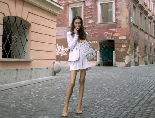 Beautiful Slovenian Fashion Blogger Veronika Lipar of Brunette from Wall dressed in all in white suit, white blazer, white tailored shorts, Stuart Weitzman high shine metallic nudist song sandals, shoulder bag while eating a croissant on the street in the morning after nuit blanche