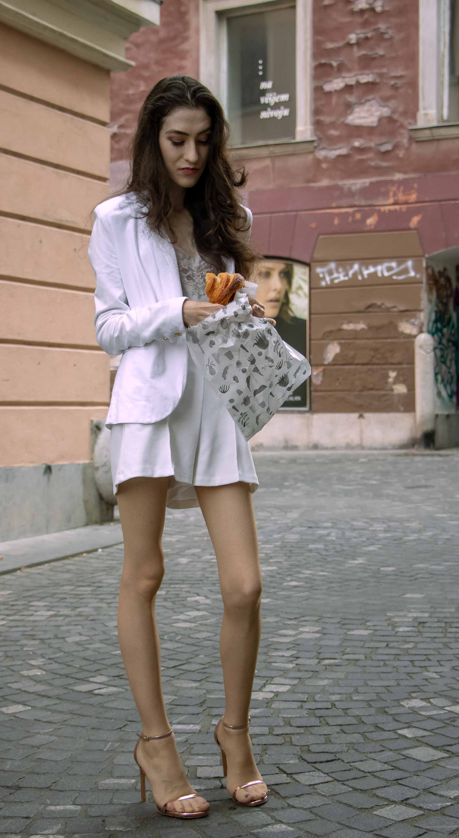 Beautiful Slovenian Fashion Blogger Veronika Lipar of Brunette from Wall wearing all in white suit, white blazer, white tailored shorts, Stuart Weitzman high shine metallic nudist song sandals, shoulder bag while eating a croissant on the street in the morning after party