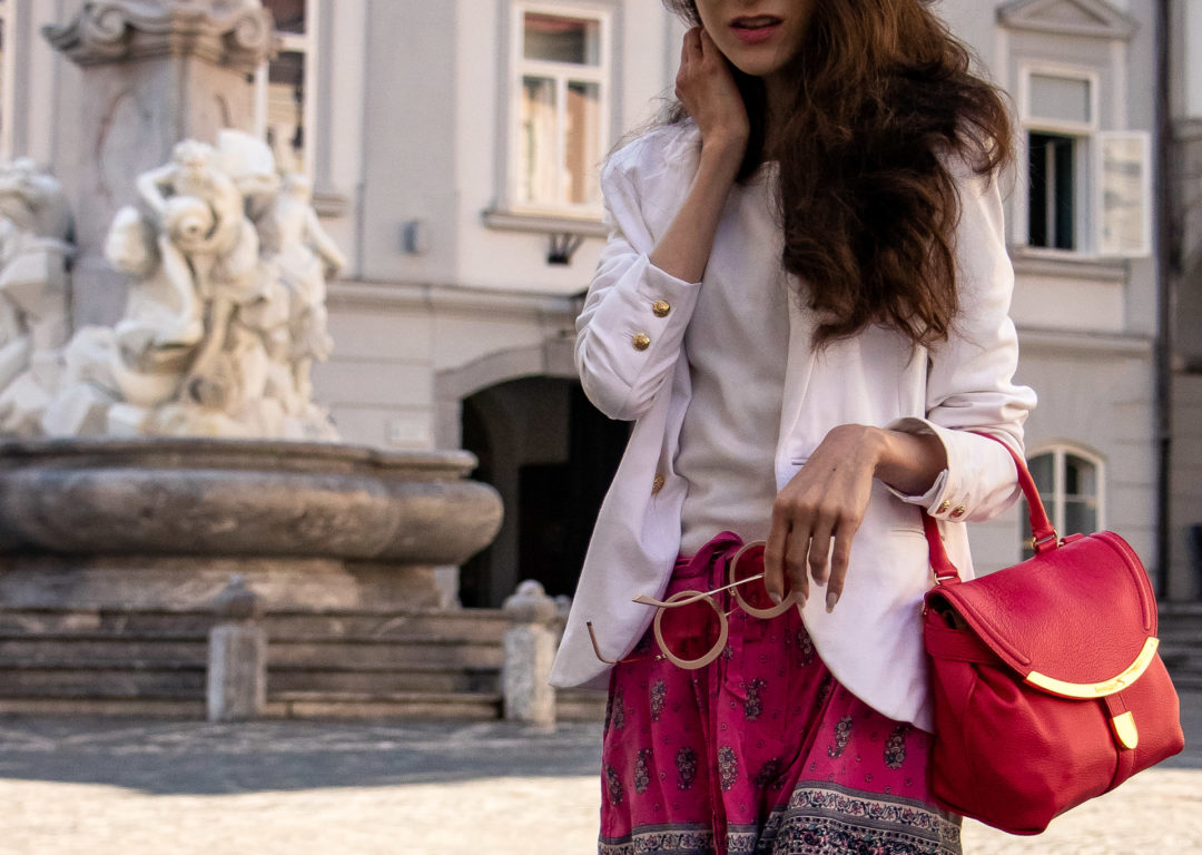 Popular Slovenian Fashion Blogger Veronika Lipar of Brunette from Wall Street wearing Juicy Couture pink print silk bermuda shorts white boatneck top white blazer pink top handle bag on the street