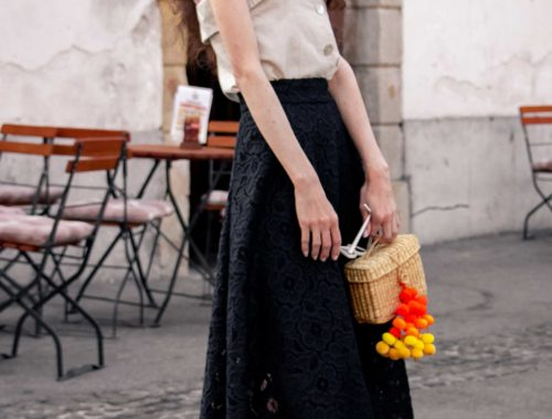 Fashion Blogger Veronika Lipar of Brunette from Wall Street wearing beige linen crop top, black lace midi skirt, Stuart Weitzman high shine metallic nudist song sandals, Nannacay basket bag, cat eye sunglasses for shopping at the grocery market