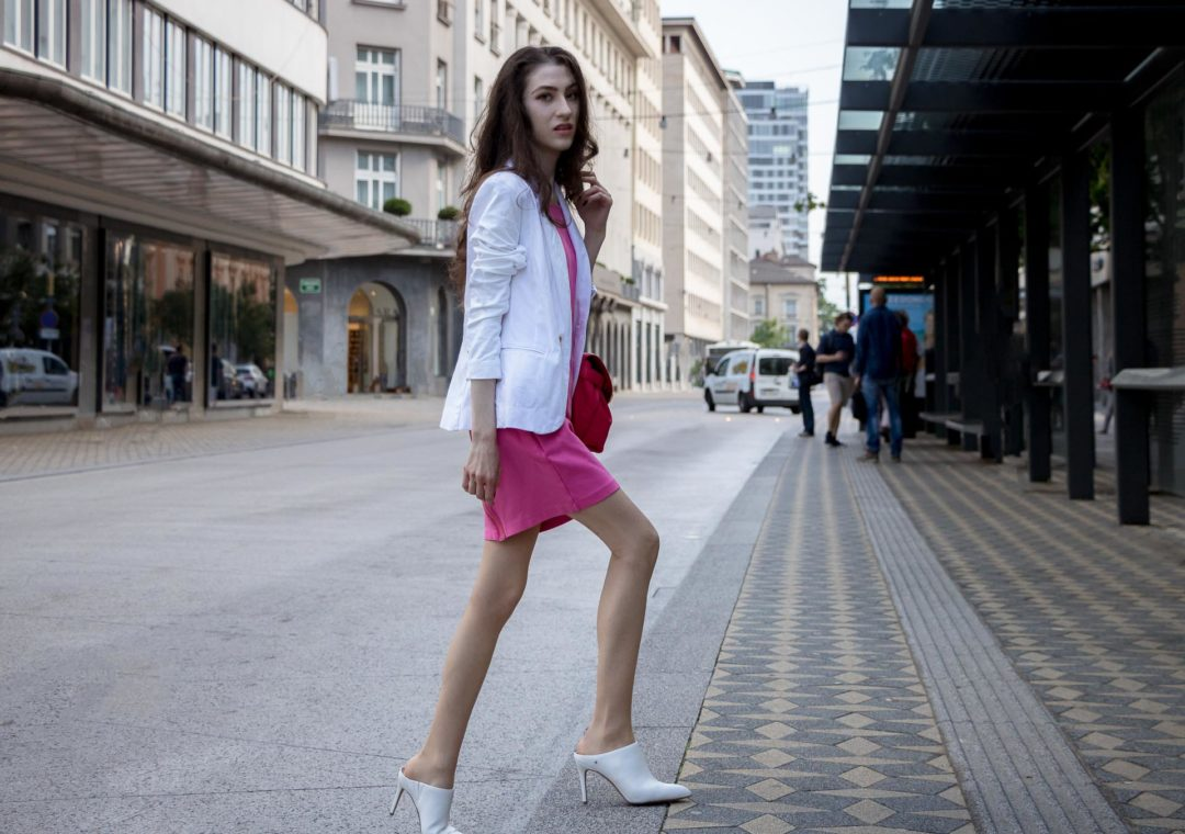 Fashion Blogger Veronika Lipar of Brunette from Wall Street dressed in white high heel close toe mules, pink tailored short dress, white blazer, pink top handle bag for work in summer