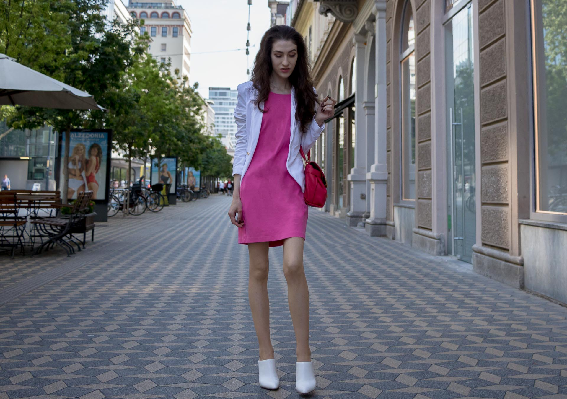 Fashion Blogger Veronika Lipar of Brunette from Wall Street dressed in summer business casual outfit, white high heel close toe mules, pink tailored short dress, white blazer, pink top handle bag standing on the street in Ljubljana