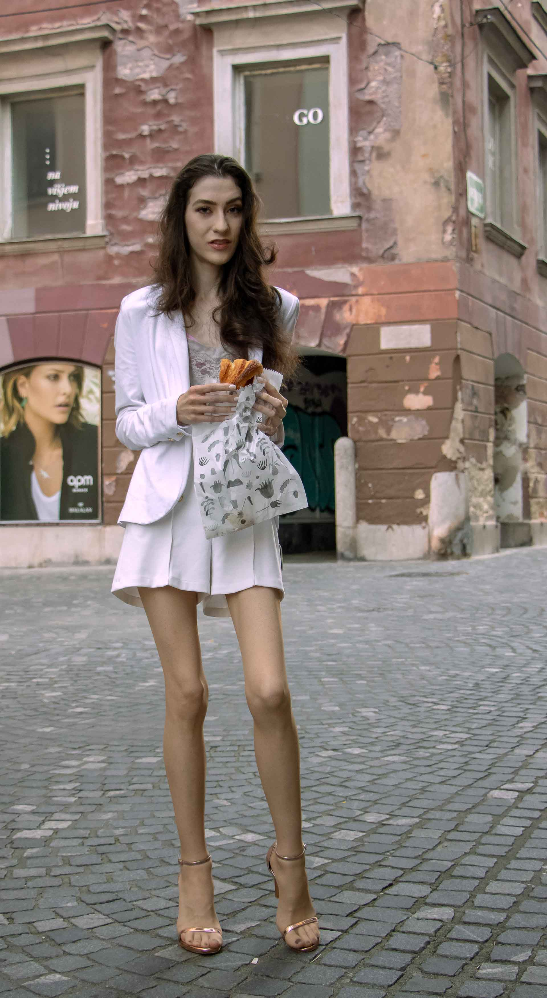 Beautiful Slovenian Fashion Blogger Veronika Lipar of Brunette from Wall wearing all in white suit, white blazer, white tailored shorts, Stuart Weitzman high shine metallic nudist song sandals, shoulder bag while eating a croissant on the street in the morning after night out clubbing