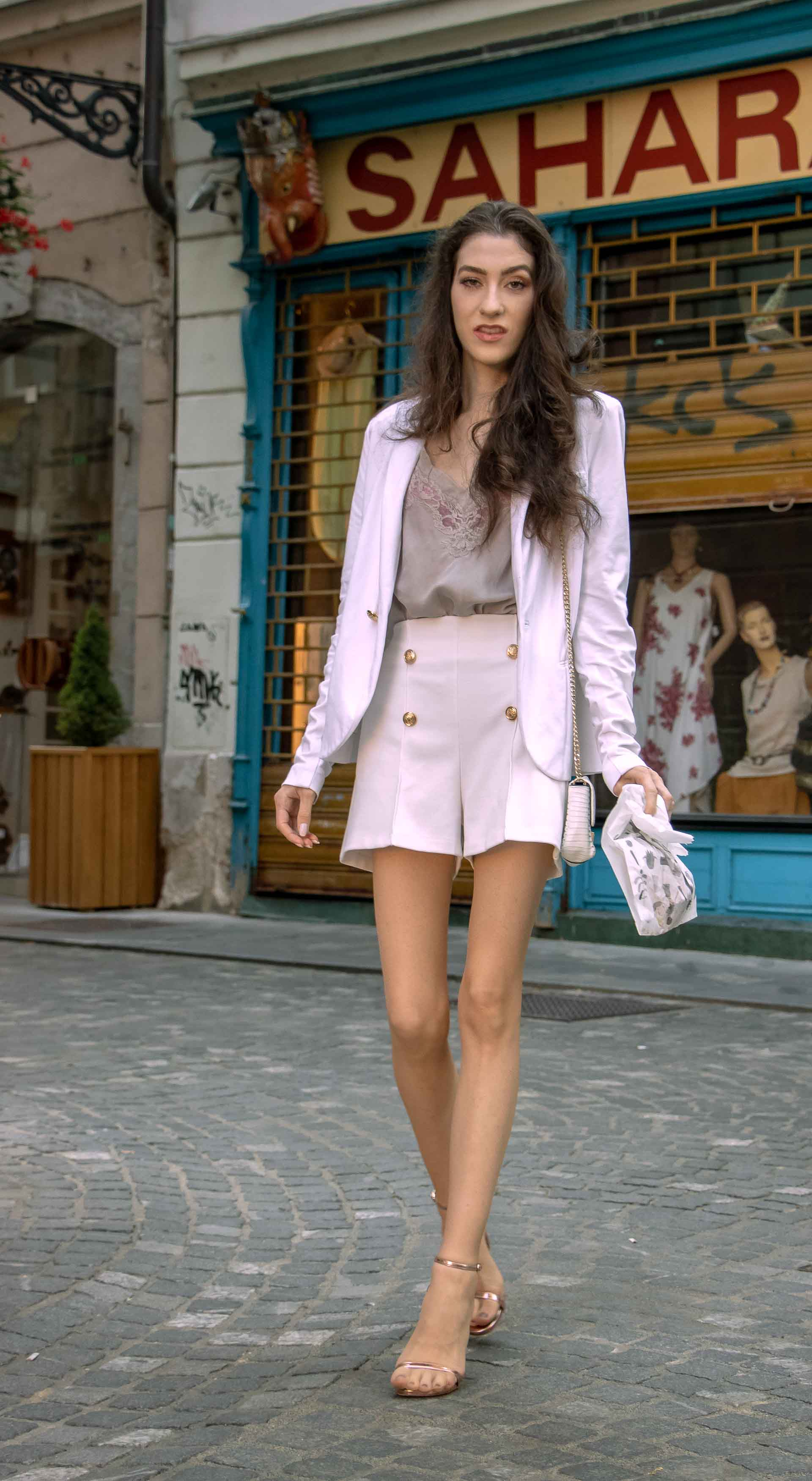 Beautiful Slovenian Fashion Blogger Veronika Lipar of Brunette from Wall dressed in all in white suit, white blazer, white tailored shorts, Stuart Weitzman high shine metallic nudist song sandals, shoulder bag with a paper bag on the street in the morning after party