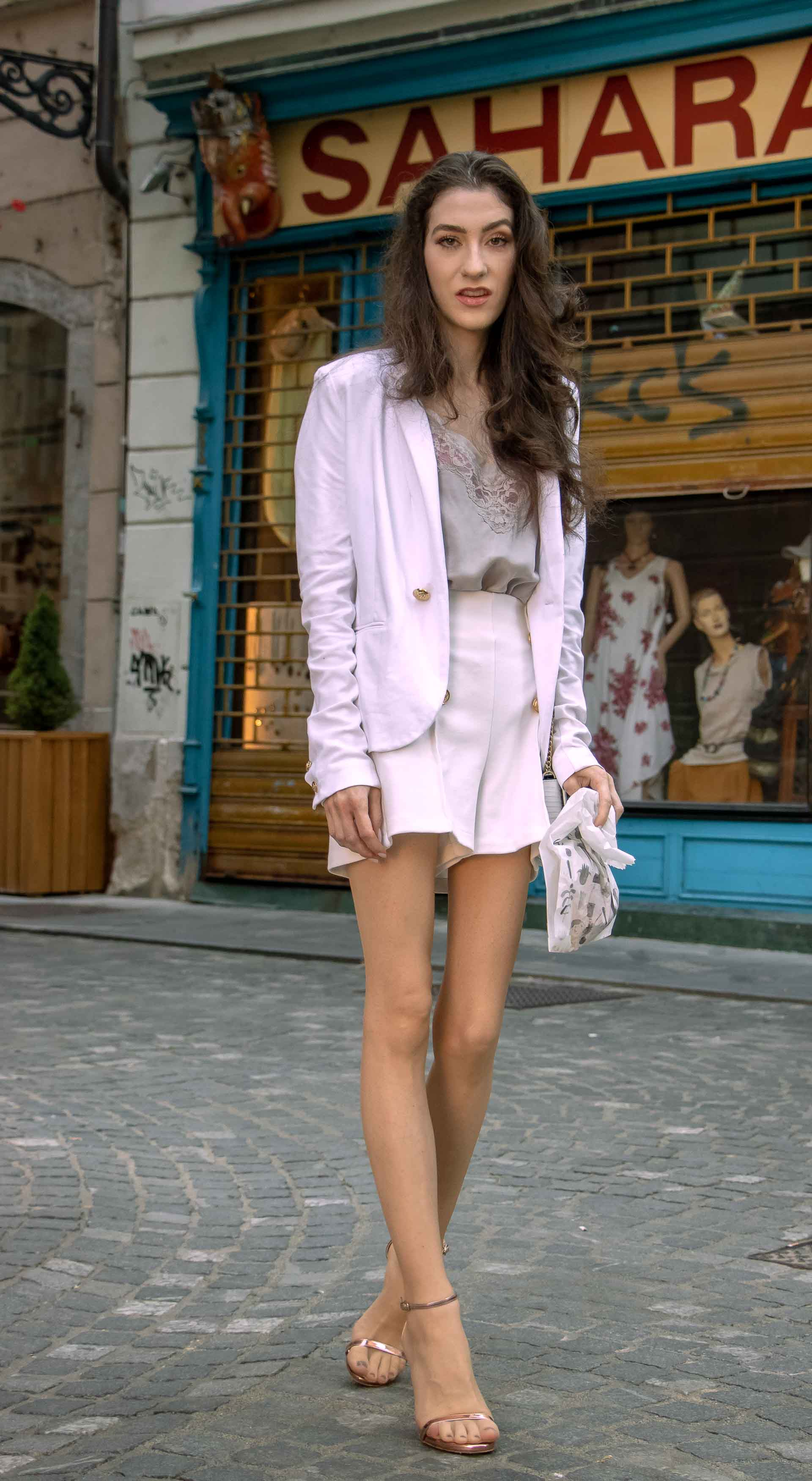 Beautiful Slovenian Fashion Blogger Veronika Lipar of Brunette from Wall wearing all in white suit, white blazer, white tailored shorts, Stuart Weitzman high shine metallic nudist song sandals, shoulder bag with a paper bag on the street in the morning after nuit blanche