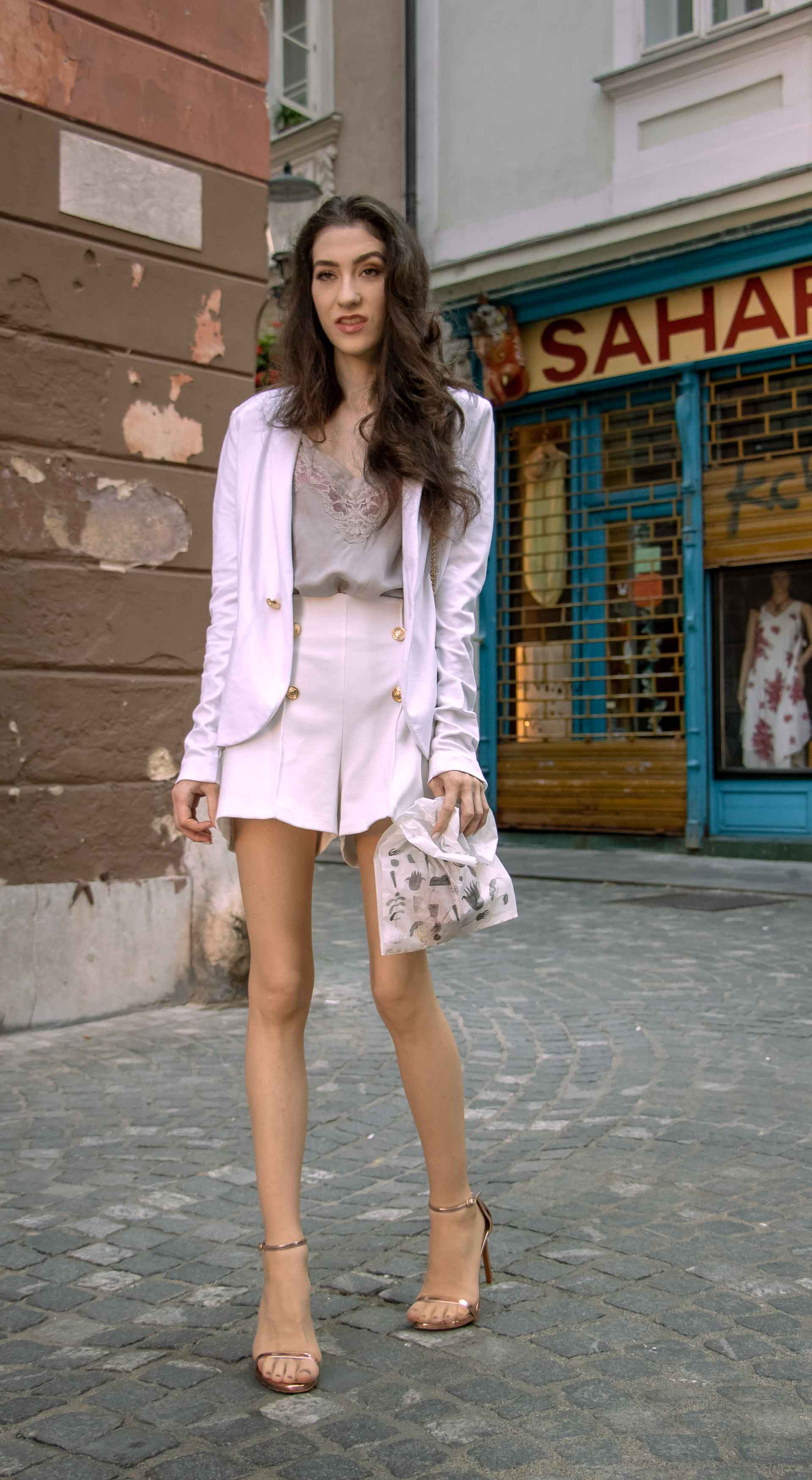 Beautiful Slovenian Fashion Blogger Veronika Lipar of Brunette from Wall dressed in all in white suit, white blazer, white tailored shorts, Stuart Weitzman high shine metallic nudist song sandals, shoulder bag with a paper bag on the street in the morning after night out