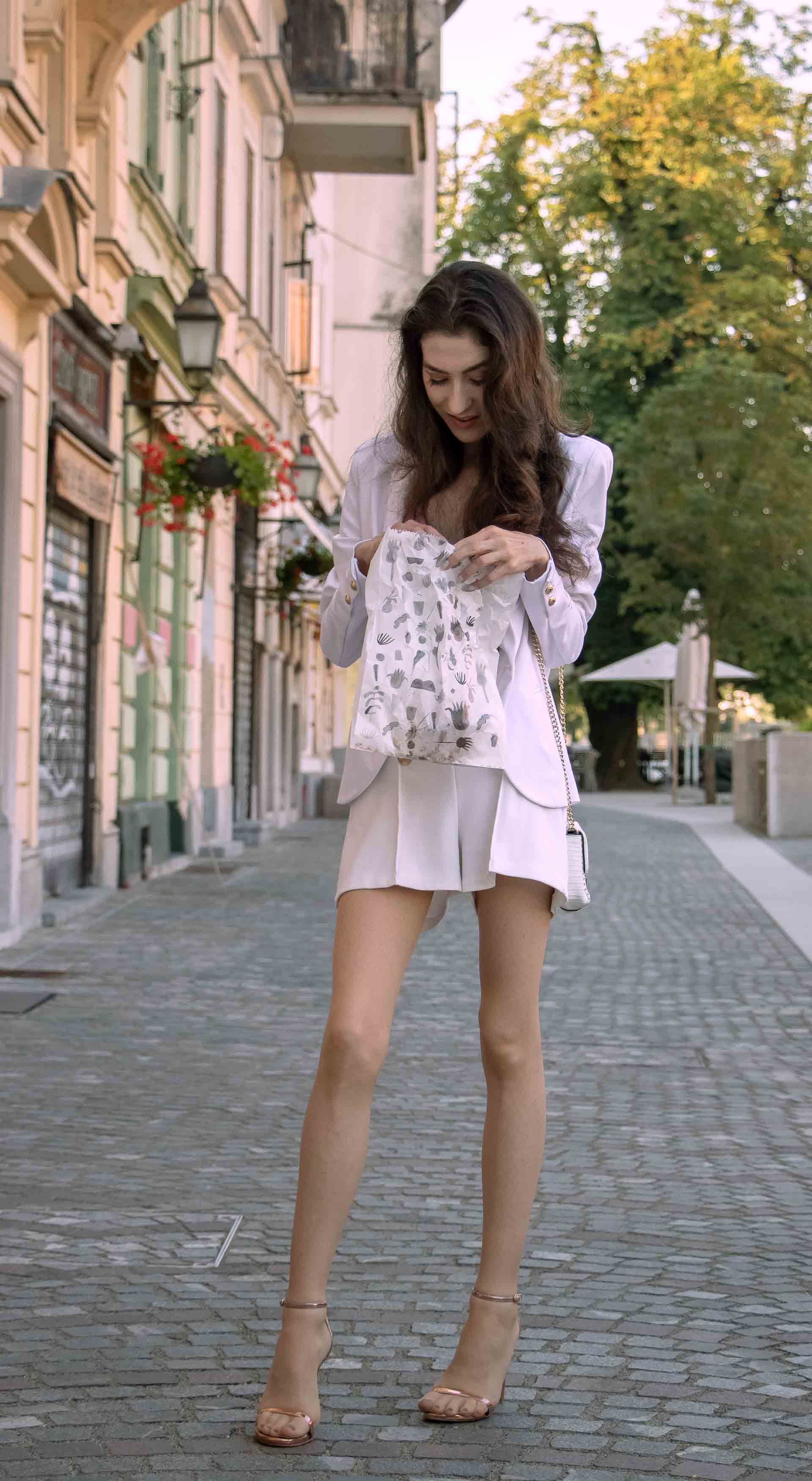Beautiful Slovenian Fashion Blogger Veronika Lipar of Brunette from Wall dressed in all in white suit, white blazer, white tailored shorts, Stuart Weitzman high shine metallic nudist song sandals, shoulder bag with a paper bag on the street in the morning after nuit blanche