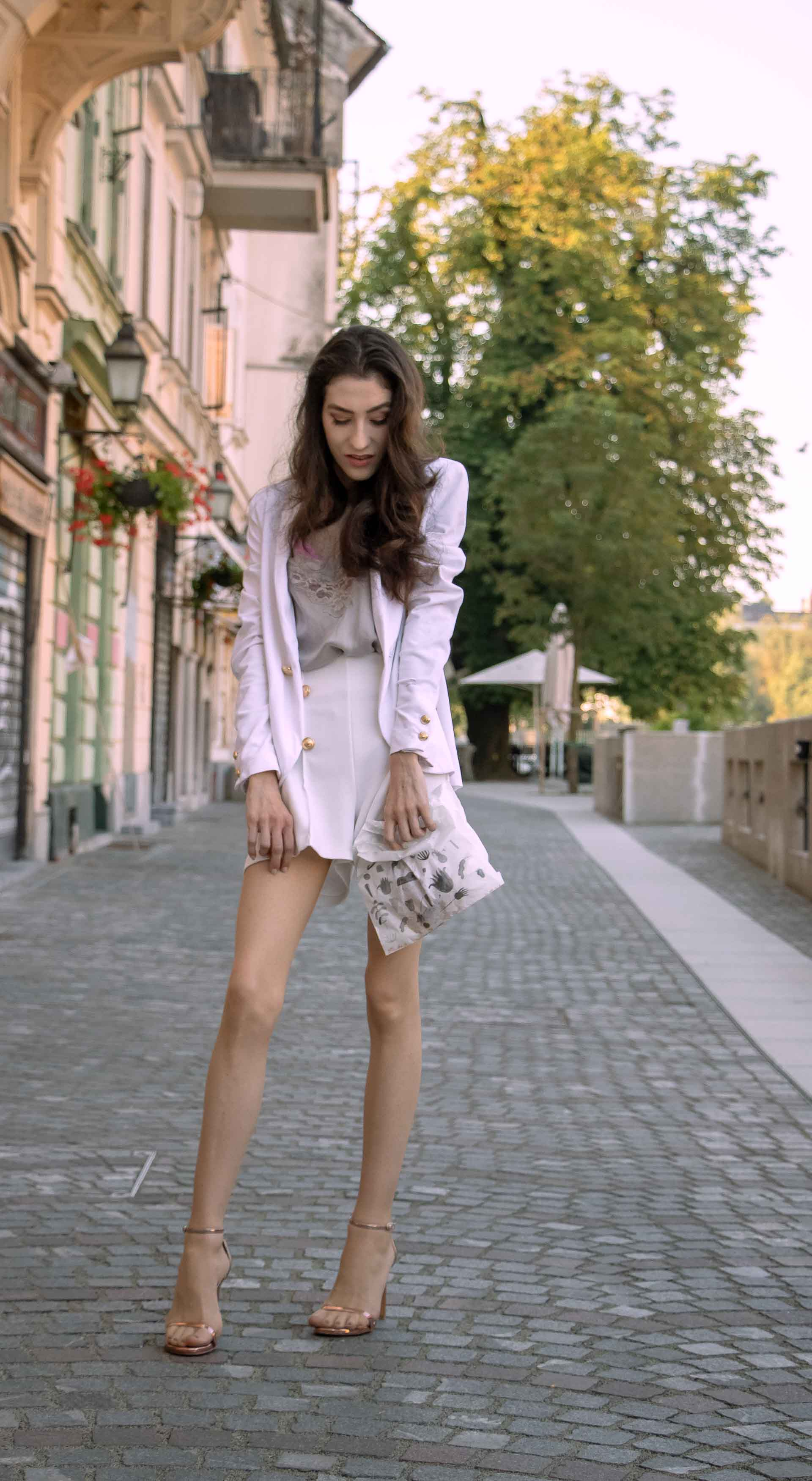 Beautiful Slovenian Fashion Blogger Veronika Lipar of Brunette from Wall dressed in all in white suit, white blazer, white tailored shorts, Stuart Weitzman high shine metallic nudist song sandals, shoulder bag holding a paper bag on the street in the morning after night out clubbing