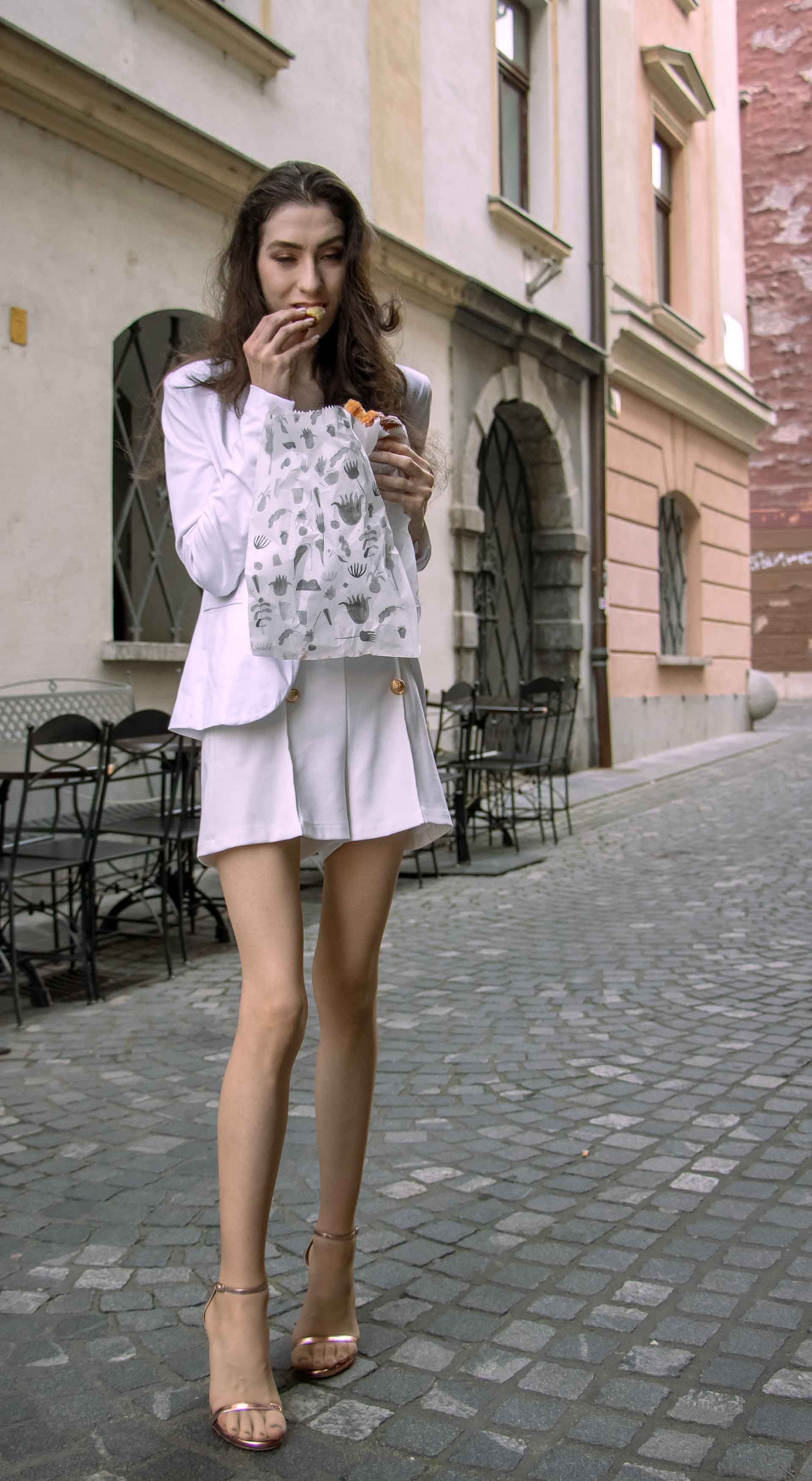 Beautiful Slovenian Fashion Blogger Veronika Lipar of Brunette from Wall dressed in all in white suit, white blazer, white tailored shorts, Stuart Weitzman high shine metallic nudist song sandals, shoulder bag while eating a croissant on the street in the morning after party