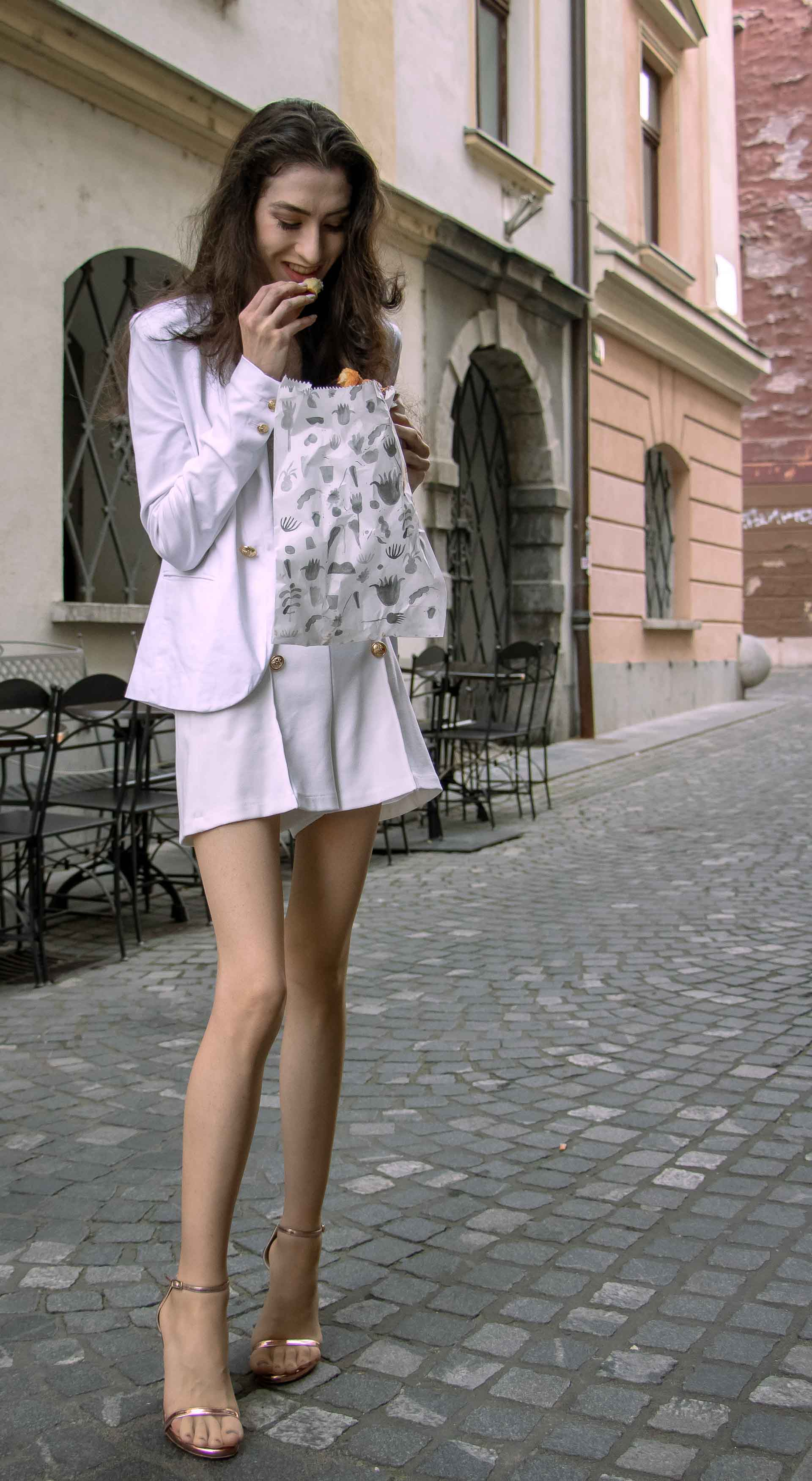 Beautiful Slovenian Fashion Blogger Veronika Lipar of Brunette from Wall dressed in all in white suit, white blazer, white tailored shorts, Stuart Weitzman high shine metallic nudist song sandals, shoulder bag while eating a croissant on the street in the morning after night out