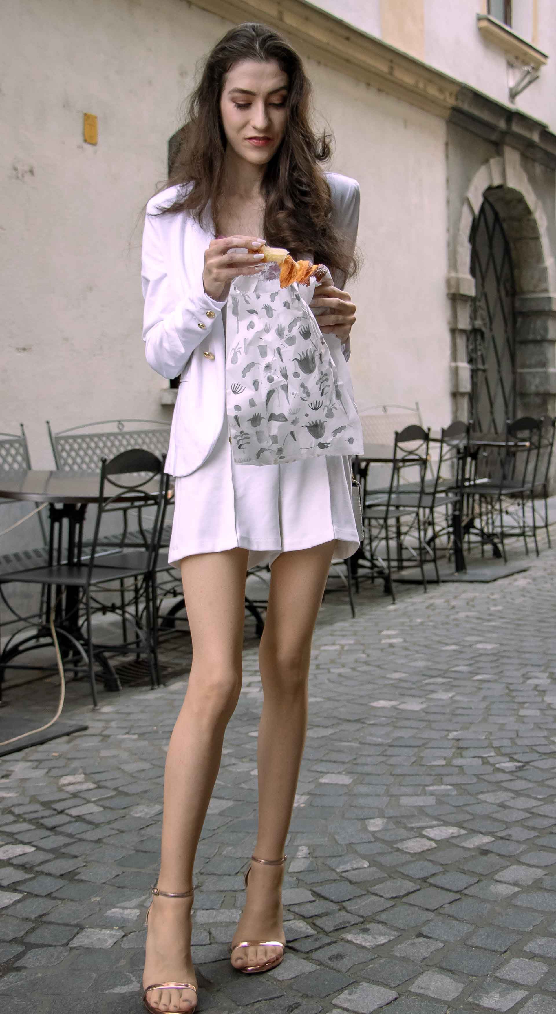 Beautiful Slovenian Fashion Blogger Veronika Lipar of Brunette from Wall wearing all in white suit, white blazer, white tailored shorts, Stuart Weitzman high shine metallic nudist song sandals, shoulder bag while eating a croissant on the street in the morning after nuit blanche