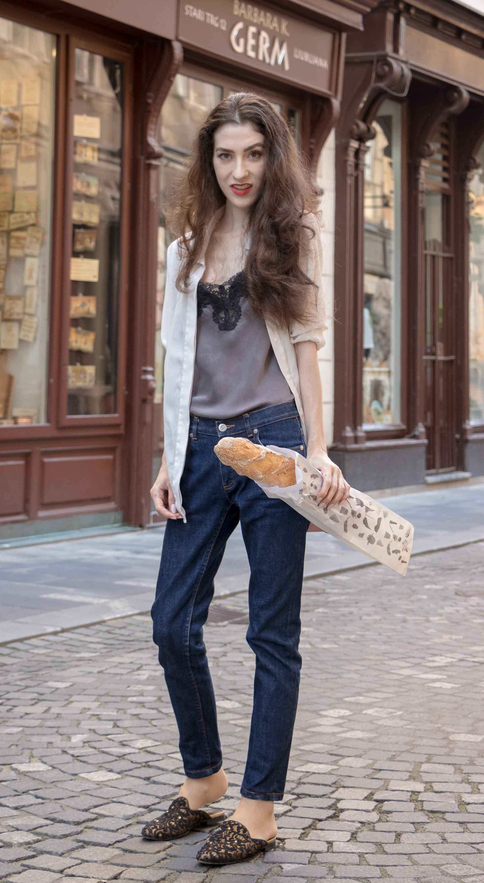 Fashion Blogger Veronika Lipar of Brunette from Wall Street wearing white sheer shirt with transparent back from Sandro Paris, grey silk slip top, A.P.C. dark denim jeans, mules, pink Furla shoulder bag, on her way from the bakery