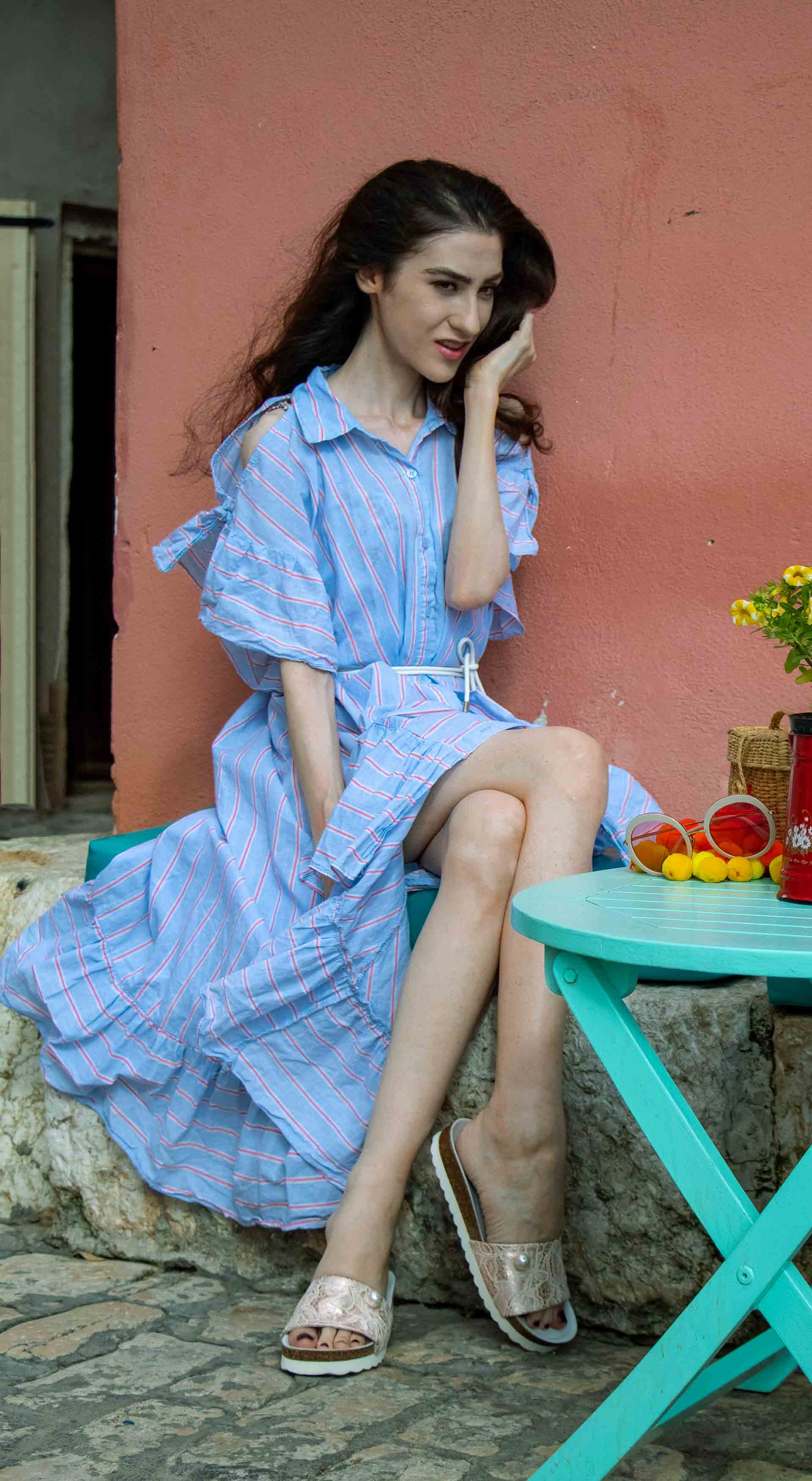 Fashion Blogger Veronika Lipar of Brunette from Wall Street dressed in Storets cold shoulder striped ruffled summer dress, blush lace pool luxe slides, Nannacay basket bag, sitting on a pastel blue bench in Rovinj