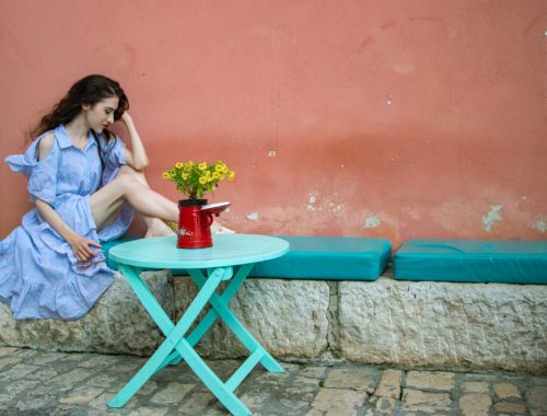 Fashion Blogger Veronika Lipar of Brunette from Wall Street wearing Storets cold shoulder striped ruffled summer dress, blush lace pool luxe slides, Nannacay basket bag, sitting on a pastel blue bench in Rovinj