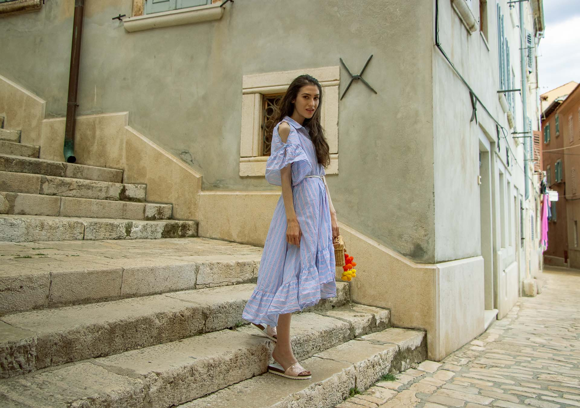 Fashion Blogger Veronika Lipar of Brunette from Wall Street dressed in Storets cold shoulder striped ruffled summer dress, blush lace pool luxe slides, Nannacay basket bag, standing on the stone paved stairs in Rovinj Croatia