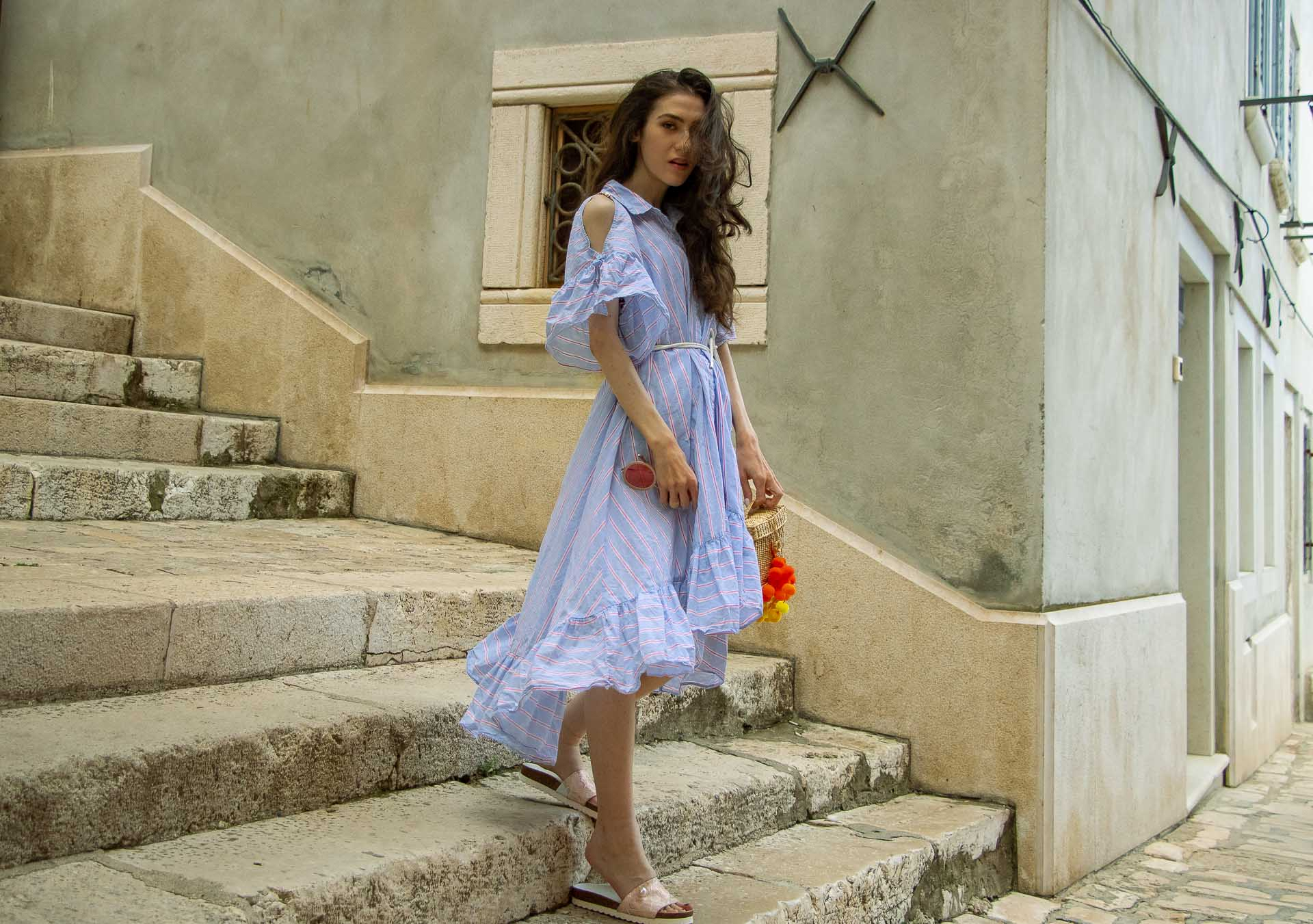 Fashion Blogger Veronika Lipar of Brunette from Wall Street wearing Storets cold shoulder striped ruffled summer dress, blush lace pool luxe slides, Nannacay basket bag, standing on the stone paved stairs in Rovinj Croatia