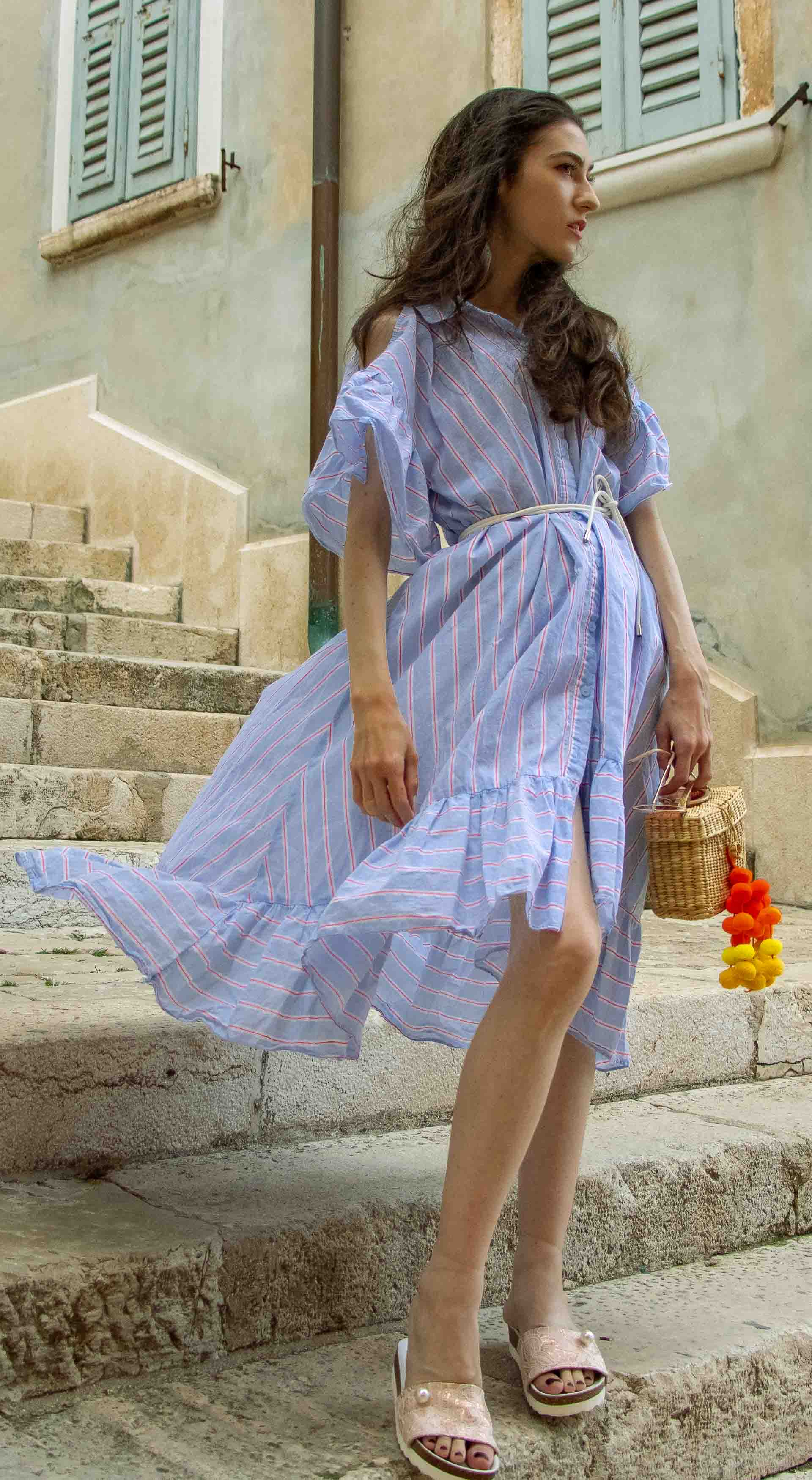 Fashion Blogger Veronika Lipar of Brunette from Wall Street dressed in Storets cold shoulder striped ruffled summer dress, blush lace pool luxe slides, Nannacay basket bag in Rovinj