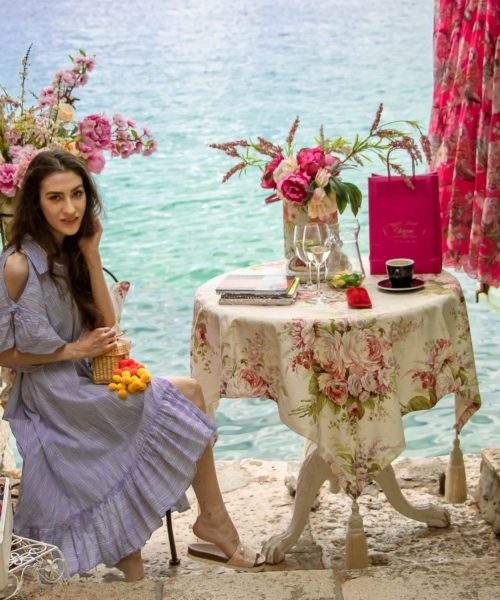 Fashion Blogger Veronika Lipar of Brunette from Wall Street dressed in Storets cold shoulder striped ruffled summer dress, blush lace pool luxe slides, Nannacay basket bag, sitting at the table with a sea view at the most Instagrammable spot in Rovinj Croatia
