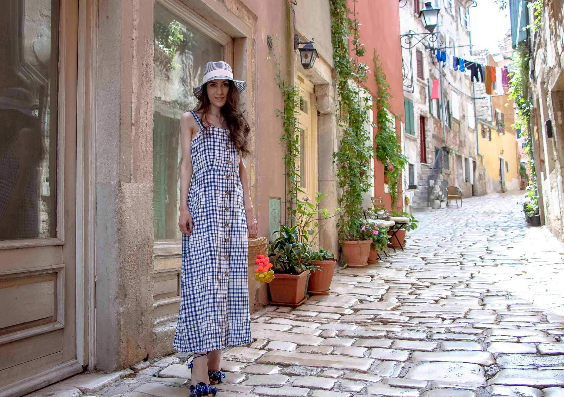 Fashion Blogger Veronika Lipar of Brunette from Wall Street dressed in plaid Mango front buttoned cotton dress, Nannacay basket bag, blue straw hat, Aquazzura blue tropicana sandals, walking down the stone paved streets in Rovinj Croatia