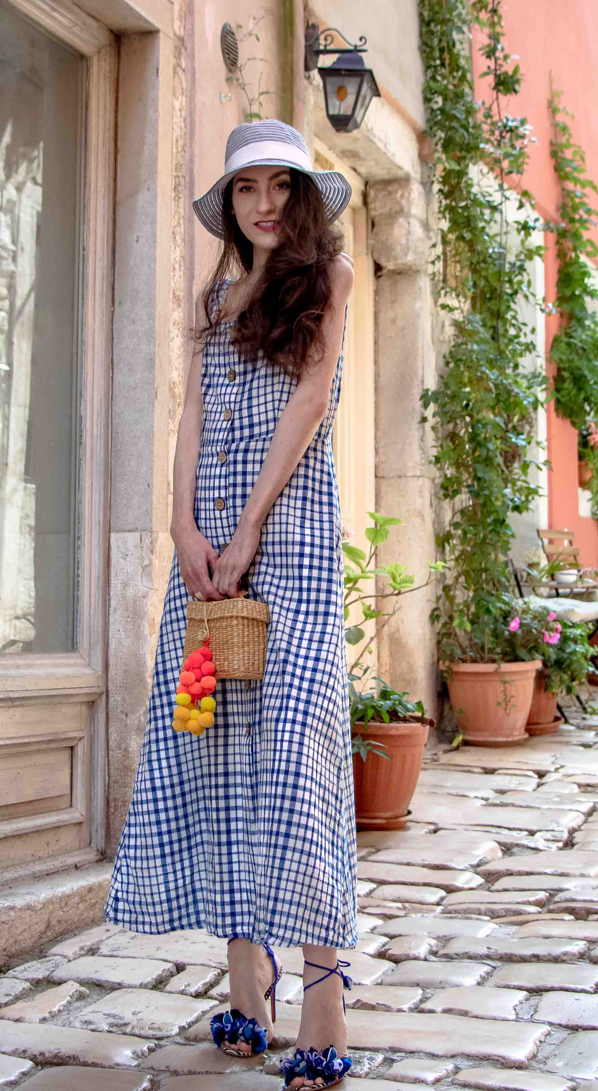 Fashion Blogger Veronika Lipar of Brunette from Wall Street wearing plaid Mango front buttoned cotton dress, Nannacay basket bag, blue straw hat, Aquazzura blue tropicana sandals, standing on the stone paved street in Rovinj Croatia