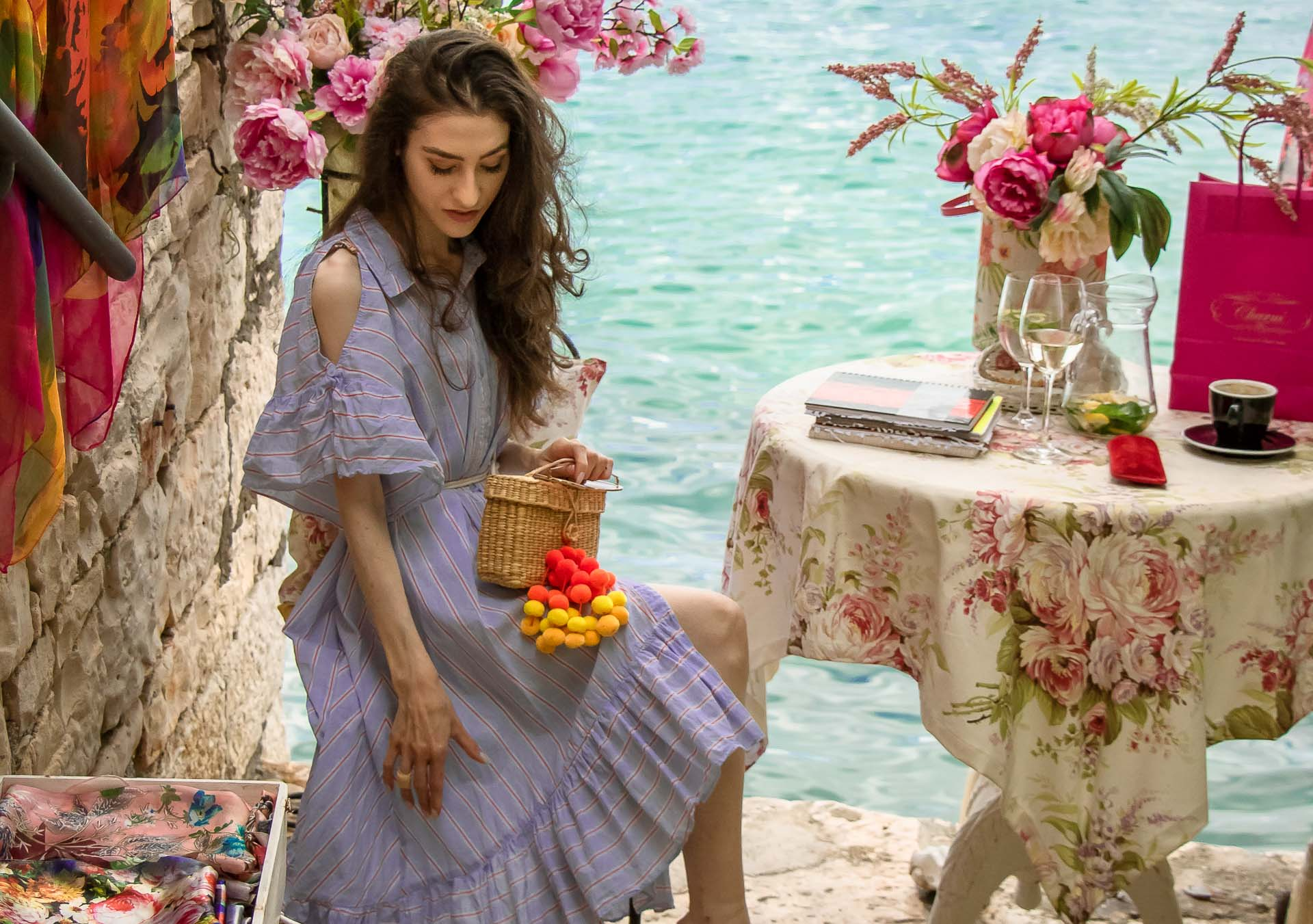 Fashion Blogger Veronika Lipar of Brunette from Wall Street wearing Storets cold shoulder striped ruffled summer dress, blush lace pool luxe slides, Nannacay basket bag, sitting at the table with a sea view at the most Instagrammable place in Rovinj Croatia