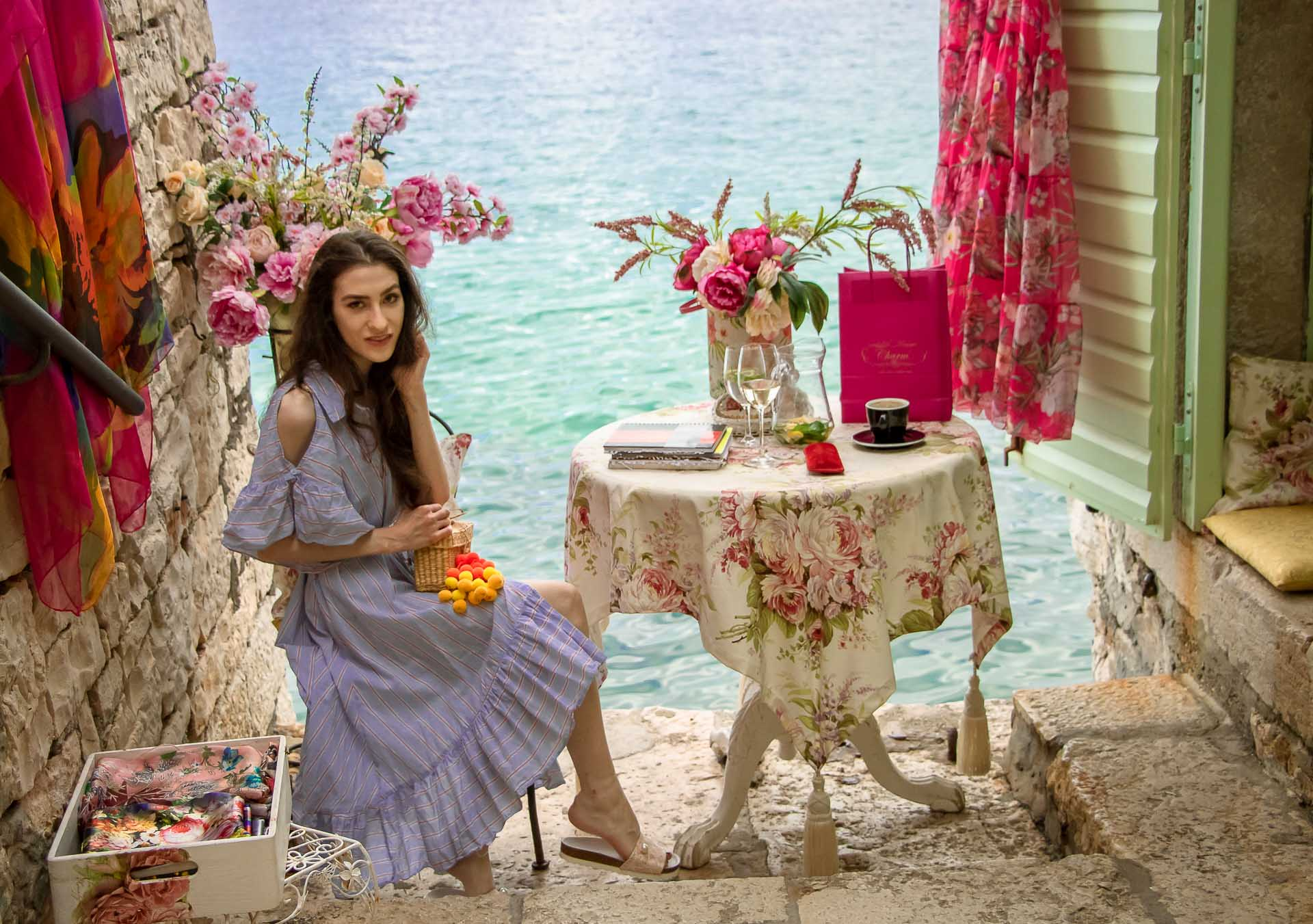 Fashion Blogger Veronika Lipar of Brunette from Wall Street dressed in Storets cold shoulder striped ruffled summer dress, blush lace pool luxe slides, Nannacay basket bag, standing in front of the table with a sea view at the most Instagrammable place in Rovinj Croatia