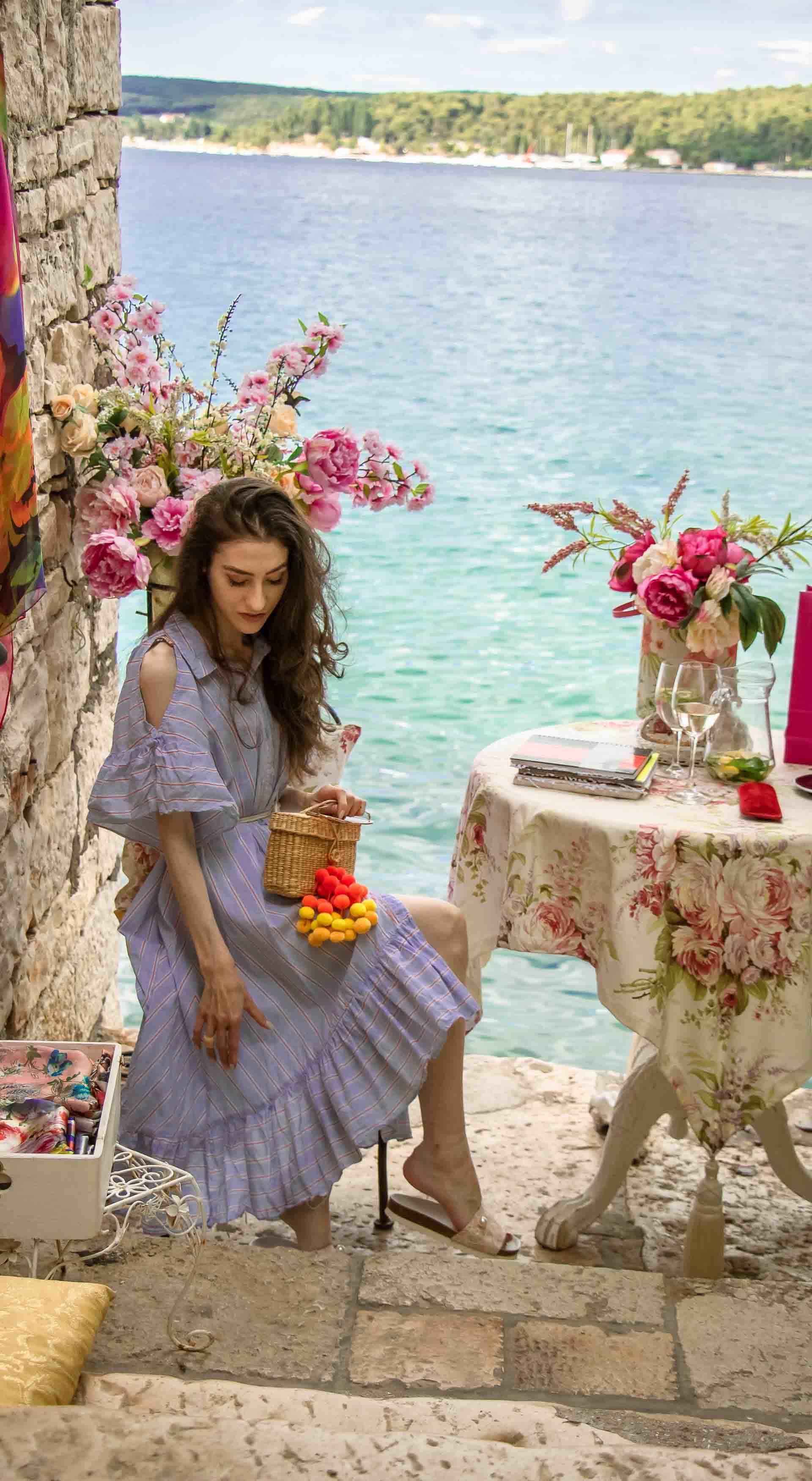 Fashion Blogger Veronika Lipar of Brunette from Wall Street wearing Storets cold shoulder striped ruffled summer dress, blush lace pool luxe slides, Nannacay basket bag, sitting at the table with a sea view at the most Instagrammable spot in Rovinj Croatia