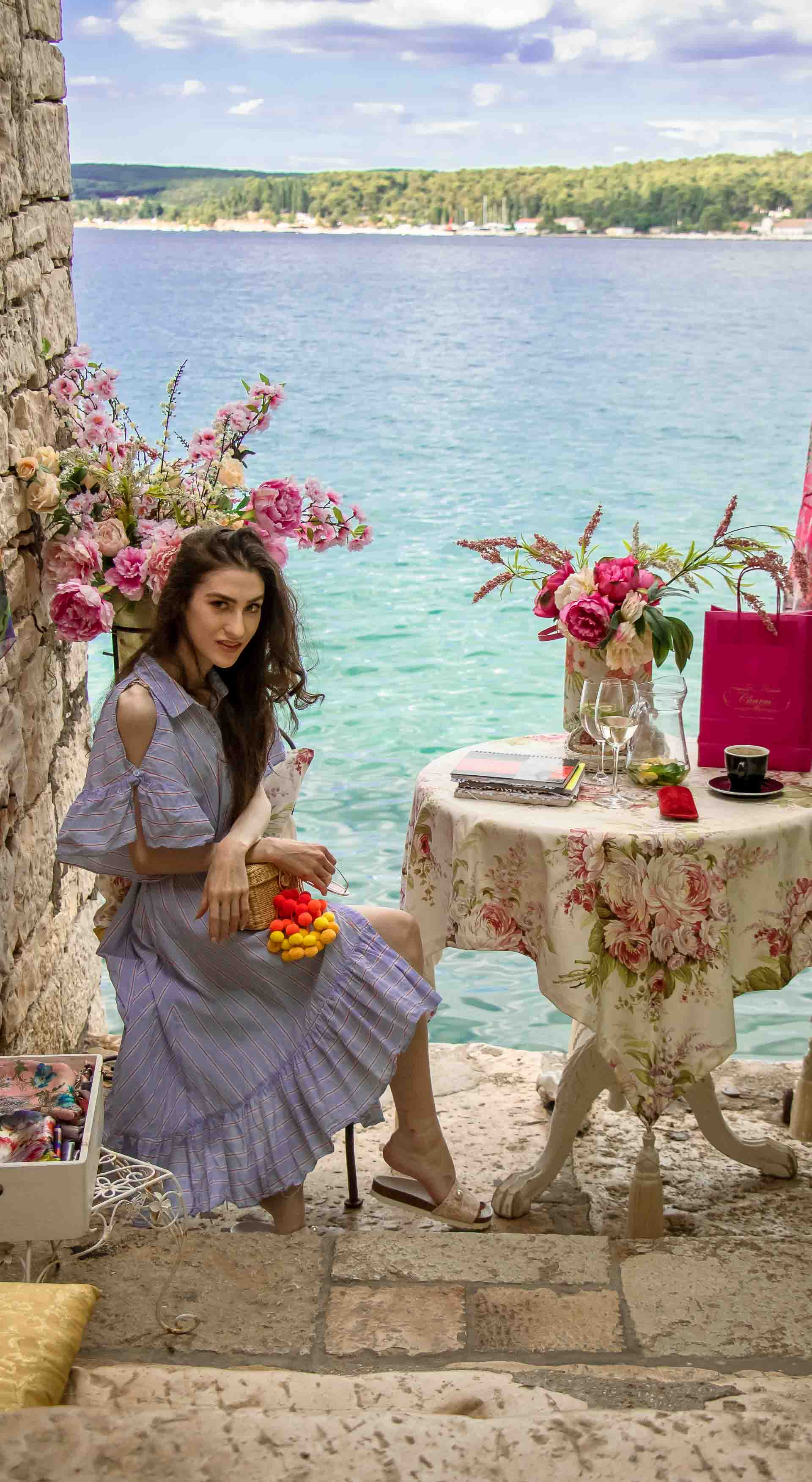 Fashion Blogger Veronika Lipar of Brunette from Wall Street dressed in Storets cold shoulder striped ruffled summer dress, blush lace pool luxe slides, Nannacay basket bag, sitting at the table with a sea view at the most Instagrammable place in Rovinj Croatia
