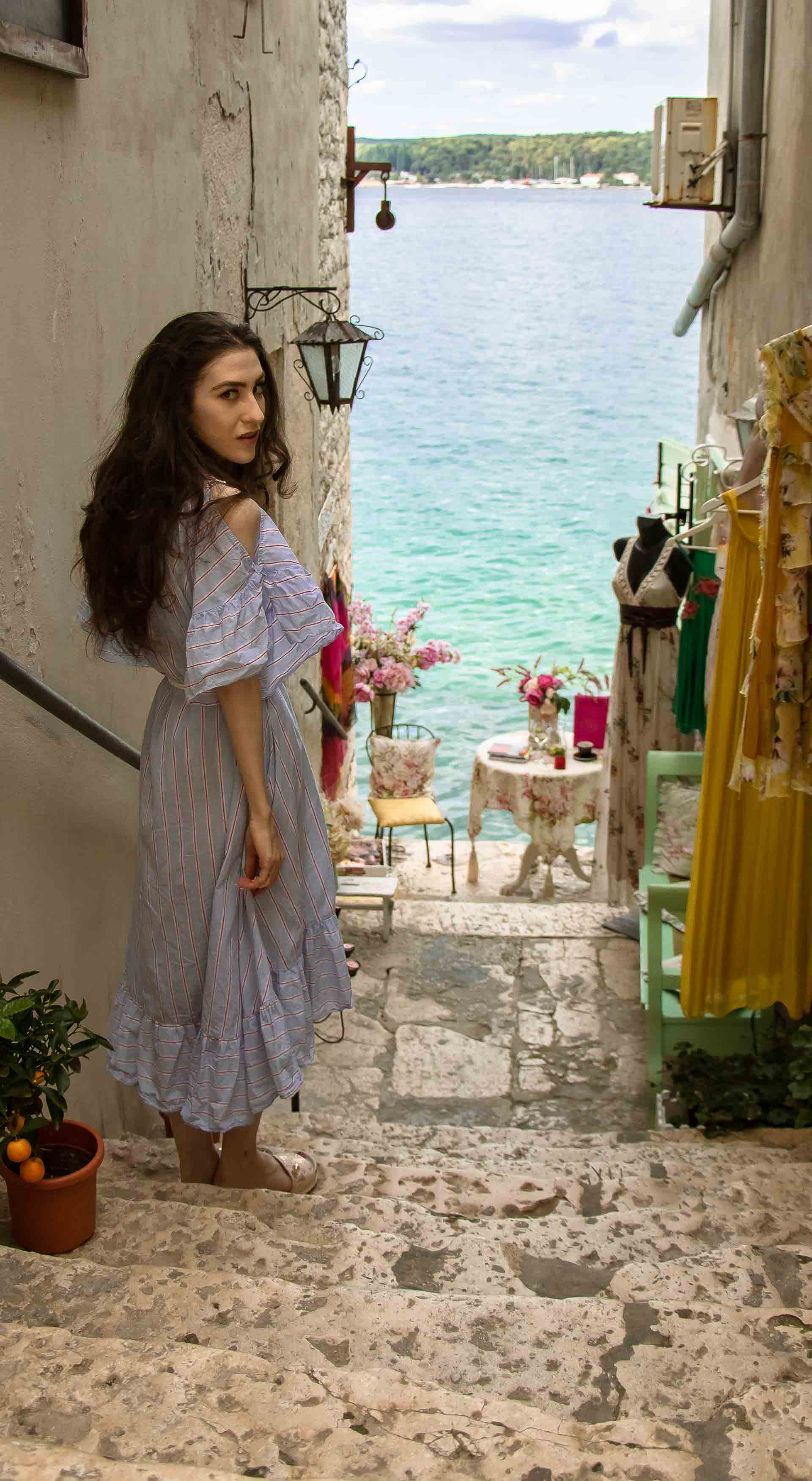 Fashion Blogger Veronika Lipar of Brunette from Wall Street wearing Storets cold shoulder striped ruffled summer dress, blush lace pool luxe slides, Nannacay basket bag, standing on the stairs in front of the table with a sea view in Rovinj Croatia