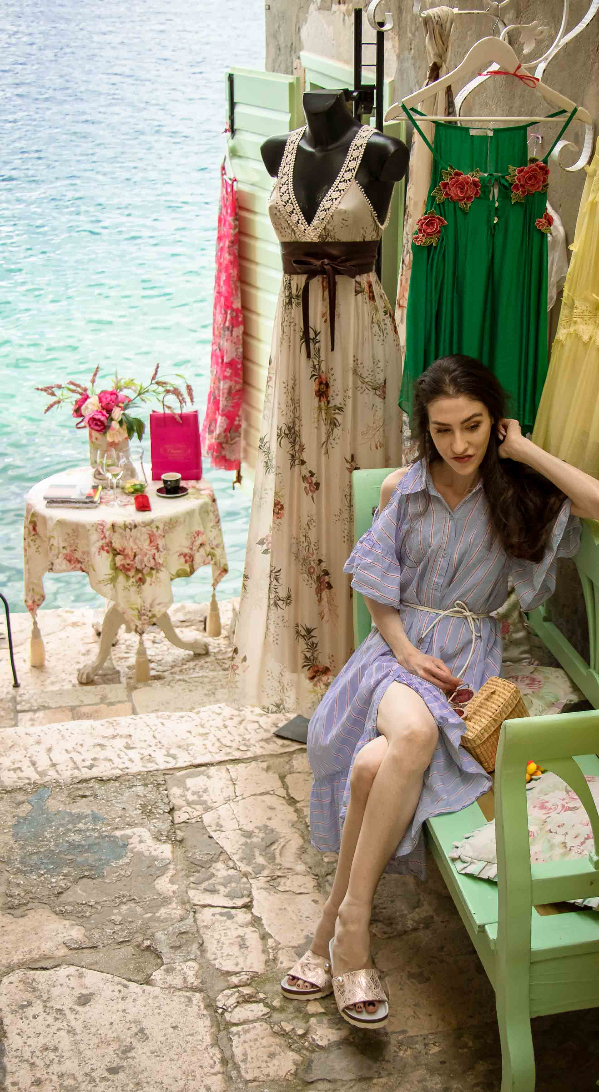 Fashion Blogger Veronika Lipar of Brunette from Wall Street wearing Storets cold shoulder striped ruffled summer dress, blush lace pool luxe slides, Nannacay basket bag, sitting on a bench in front of the most Instagrammable place in Rovinj Croatia