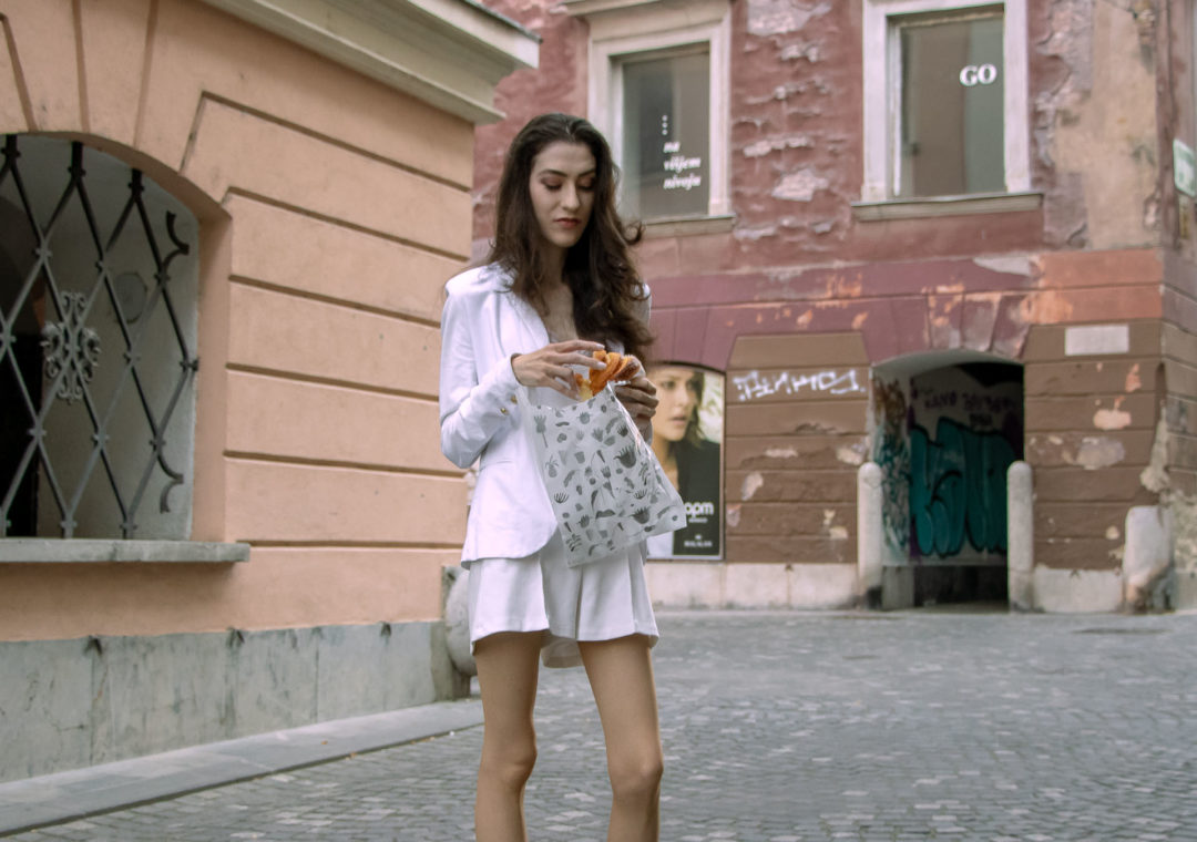 Beautiful Slovenian Fashion Blogger Veronika Lipar of Brunette from Wall wearing all in white suit, white blazer, white tailored shorts, Stuart Weitzman high shine metallic nudist song sandals, shoulder bag while eating a croissant on the street in the morning after night out