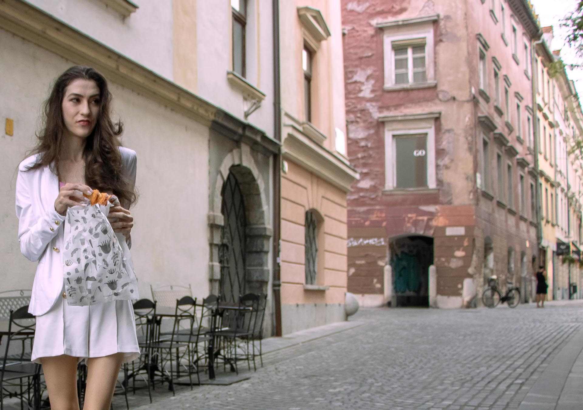 Beautiful Slovenian Fashion Blogger Veronika Lipar of Brunette from Wall dressed in all in white suit, white blazer, white tailored shorts, Stuart Weitzman high shine metallic nudist song sandals, shoulder bag while eating a croissant on the street in the morning after night out clubbing