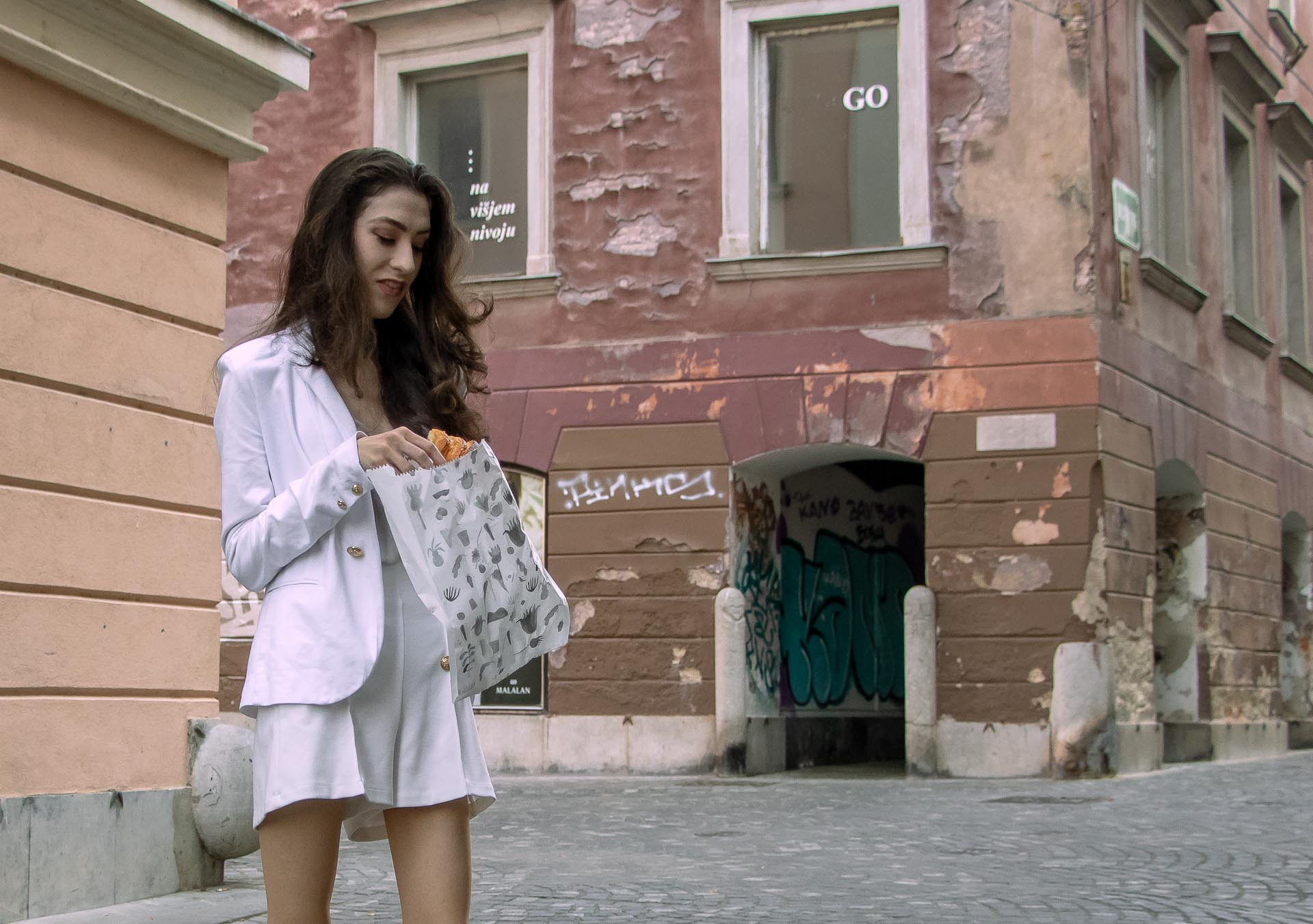 Beautiful Slovenian Fashion Blogger Veronika Lipar of Brunette from Wall wearing all in white suit, white blazer, white tailored shorts, shoulder bag while eating a croissant on the street in the morning after night out clubbing