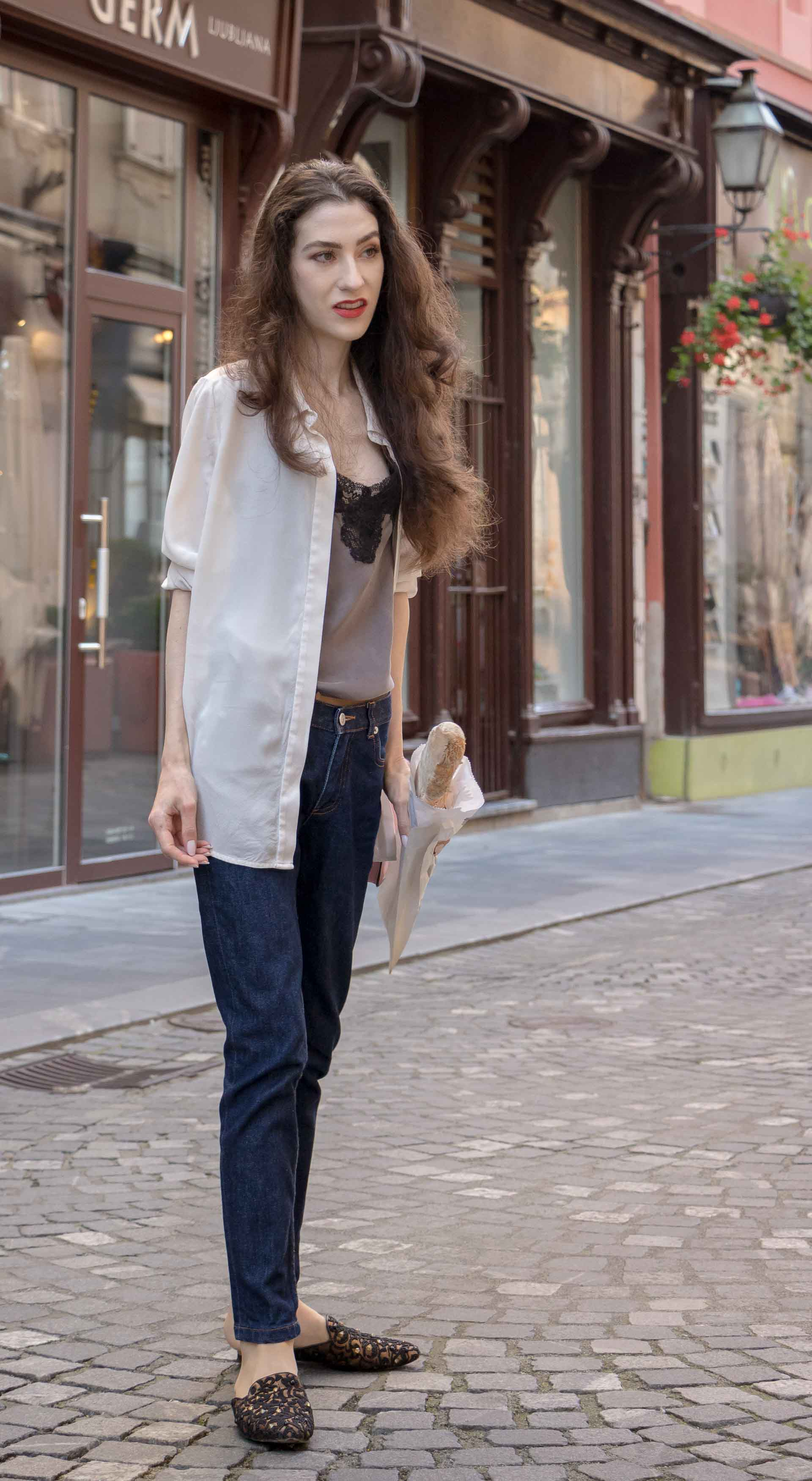 Fashion Blogger Veronika Lipar of Brunette from Wall Street dressed in white transparent shirt with transparent back from Sandro Paris, grey silk slip top, A.P.C. dark denim jeans, mules, pink Furla shoulder bag, while holding a baguette on the street