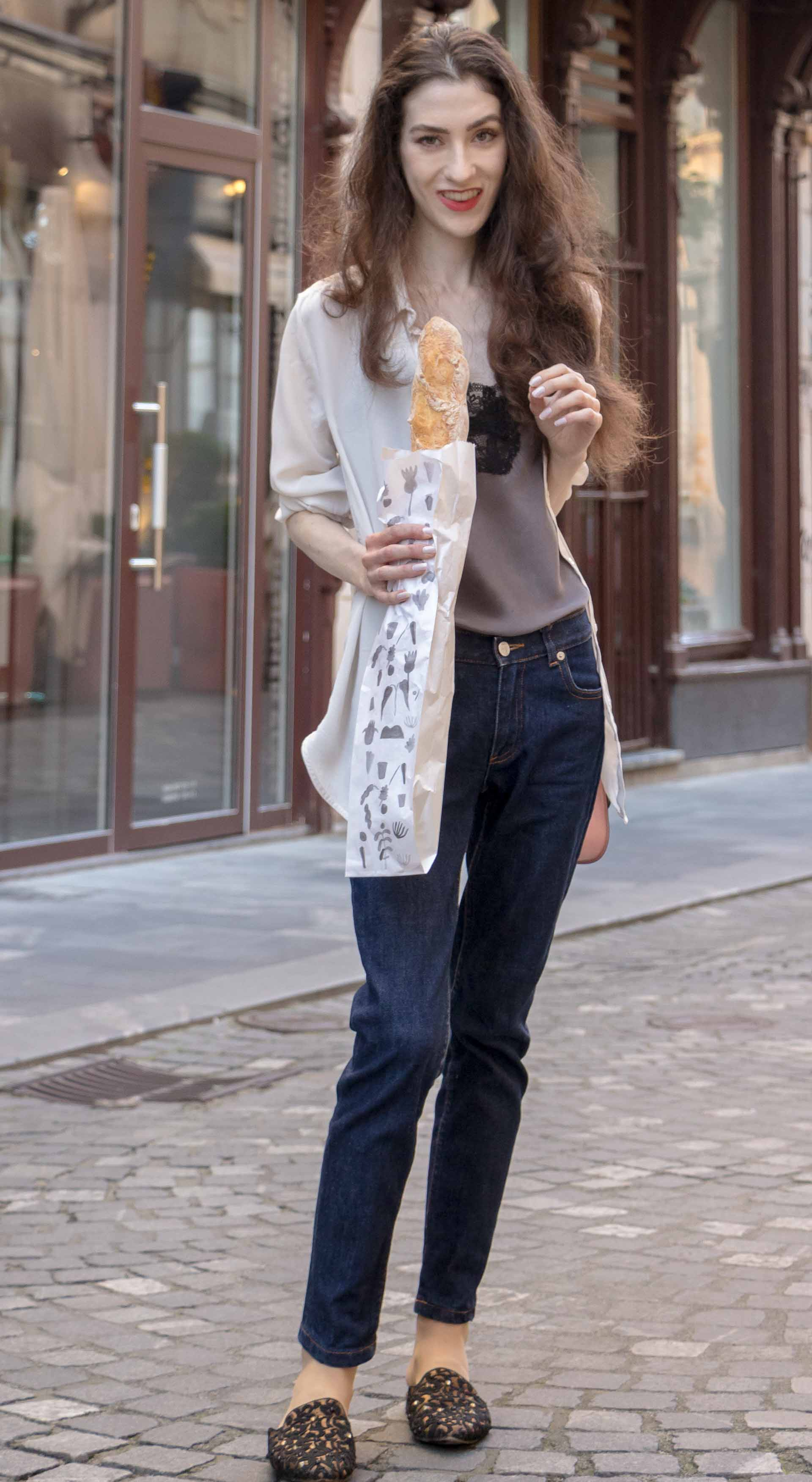 Fashion Blogger Veronika Lipar of Brunette from Wall Street wearing white organza shirt with transparent back from Sandro Paris, grey silk slip top, A.P.C. dark denim jeans, mules, pink Furla shoulder bag, while holding a baguette on the street