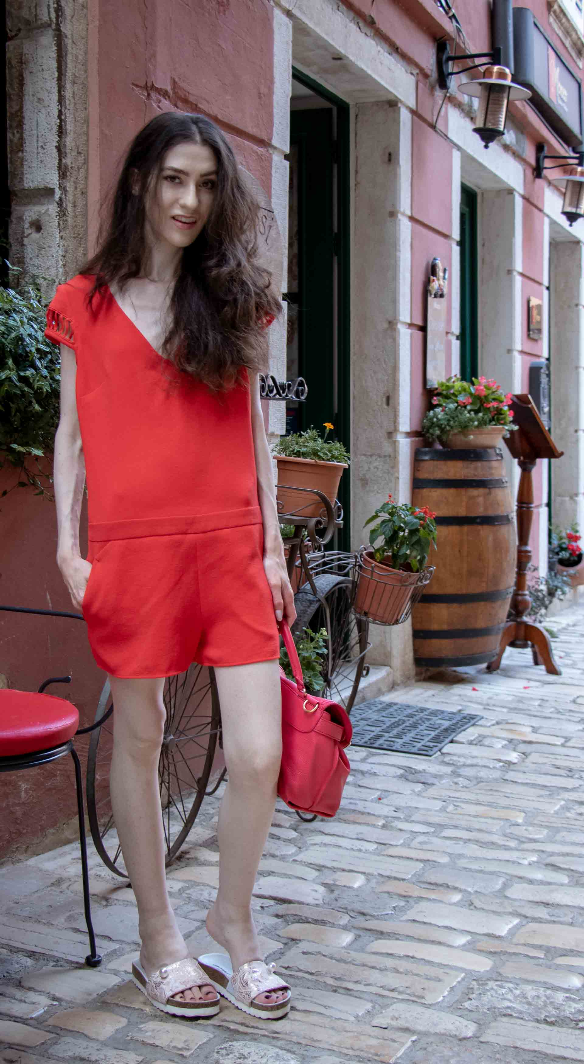 Fashion Blogger Veronika Lipar of Brunette from Wall Street dressed in open back chic red romper, crystal-embellished lace luxe pool slides, pink top handle bag while standing on the narrow picturesque street in Rovinj